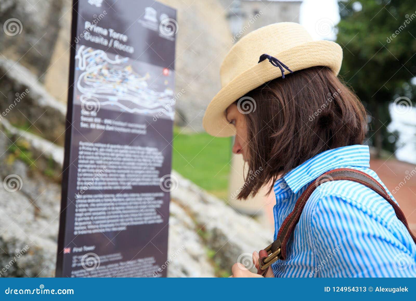 L information de touristes de lecture de fille de la forteresse du Saint-Marin