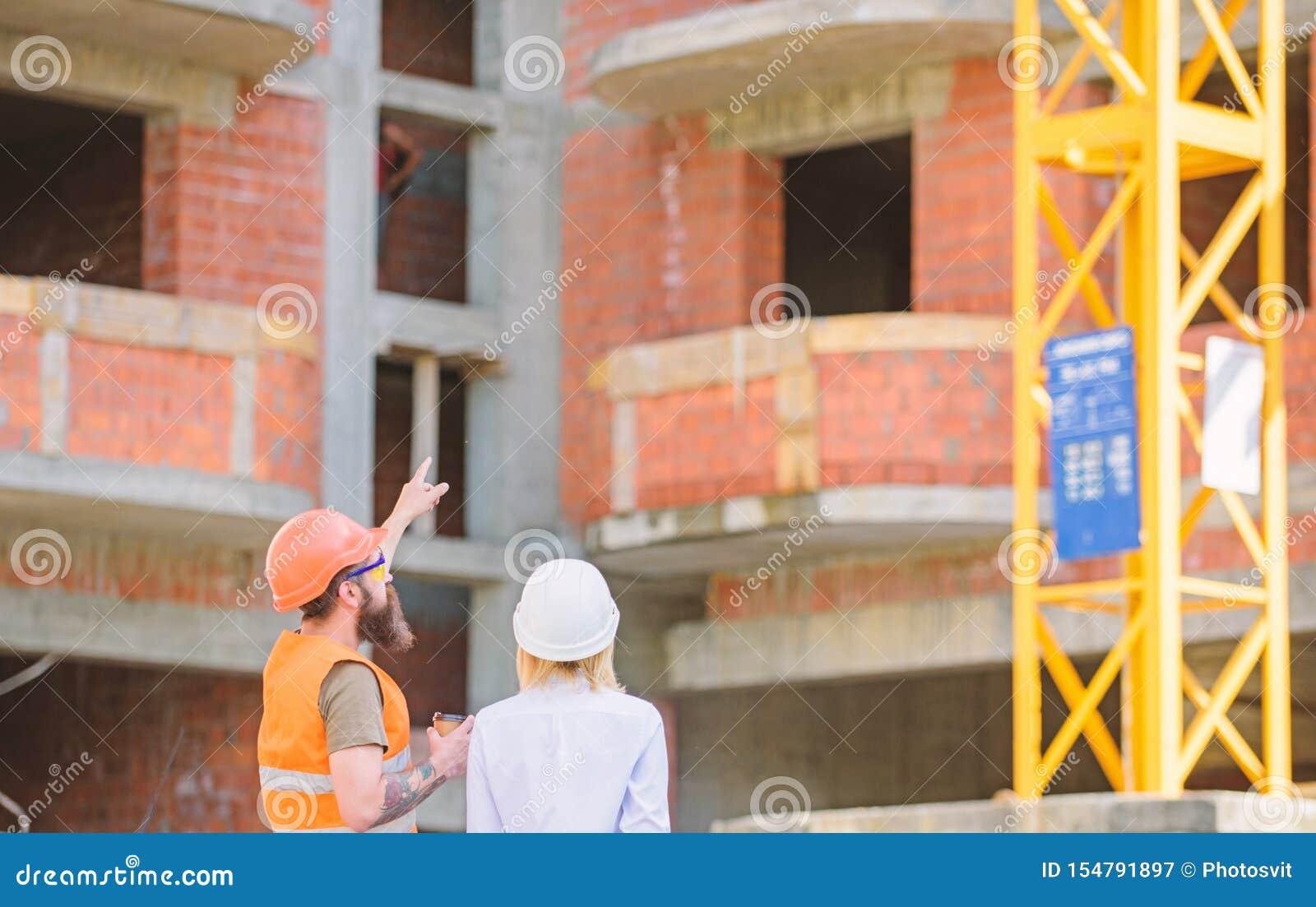 L ing?nieur et le constructeur de femme communiquent au chantier de construction Relations entre les clients de construction et l