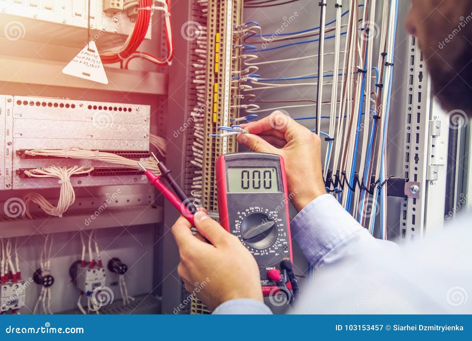 L ingegnere collauda il gabinetto elettrico industriale Cavo a disposizione dell elettricista con il multimetro Professionista in