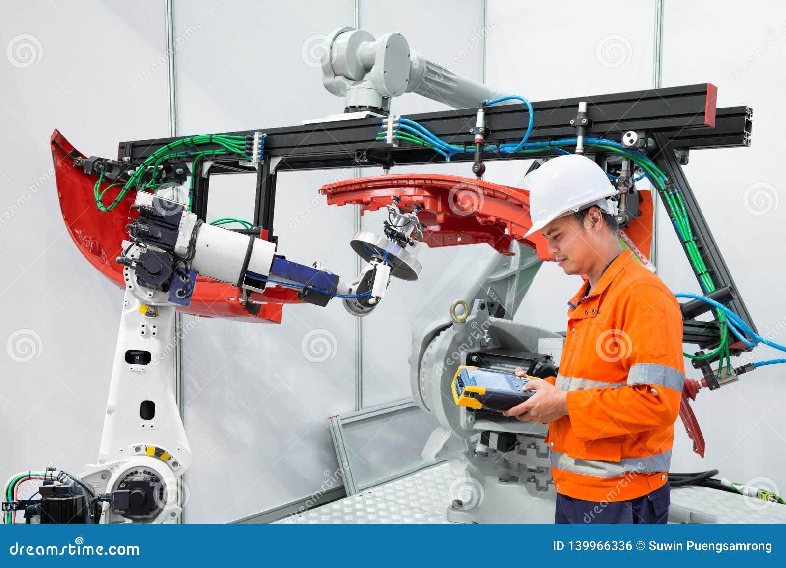 L ingegnere facendo uso dello strumento di misura ispeziona il pezzo in lavorazione automobilistico della presa del robot industr