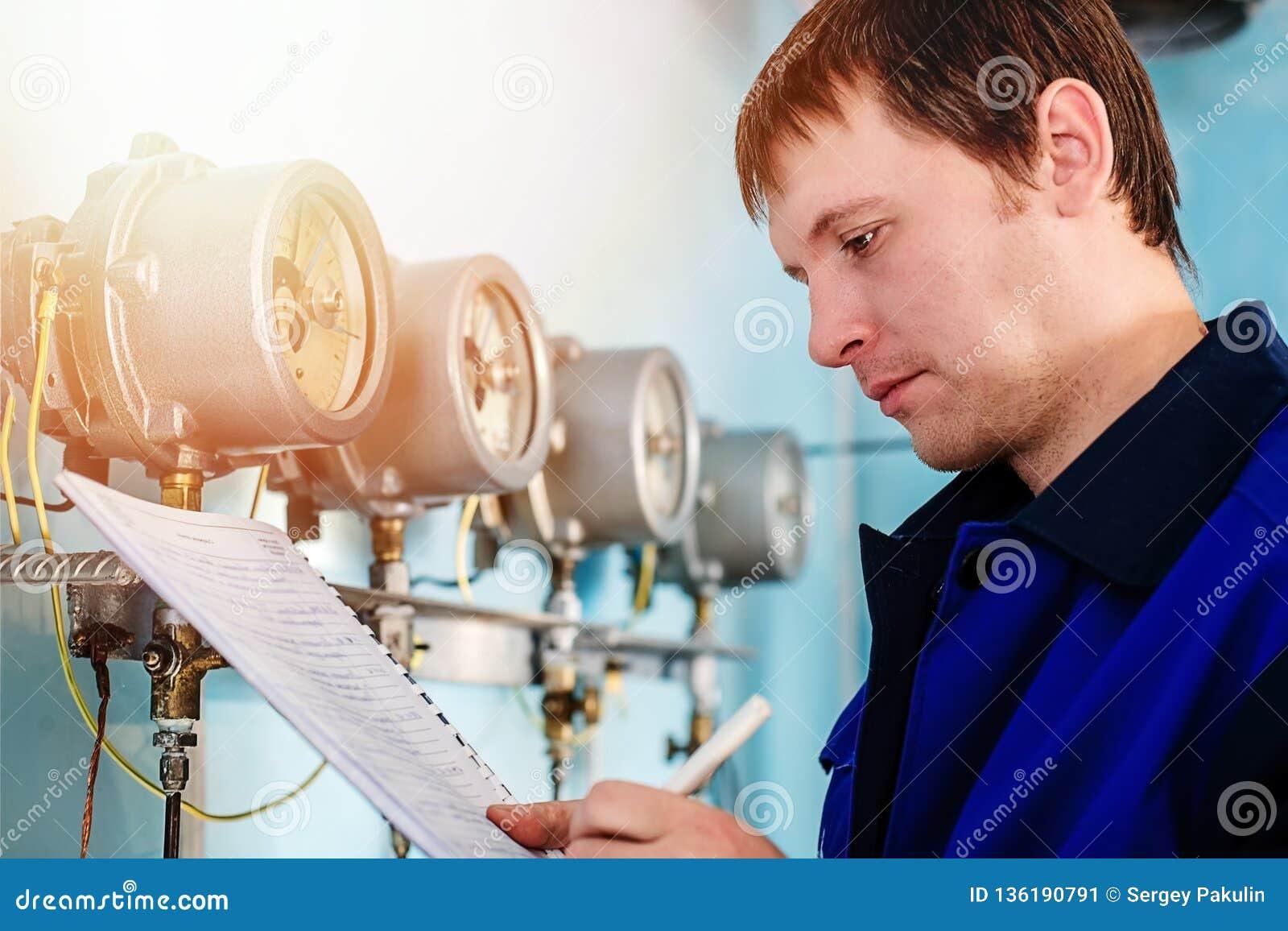 L ingegnere, lavoratore registra le letture dei sensori e dei manometri Controllo del rifornimento idrico e del sistema di riscal