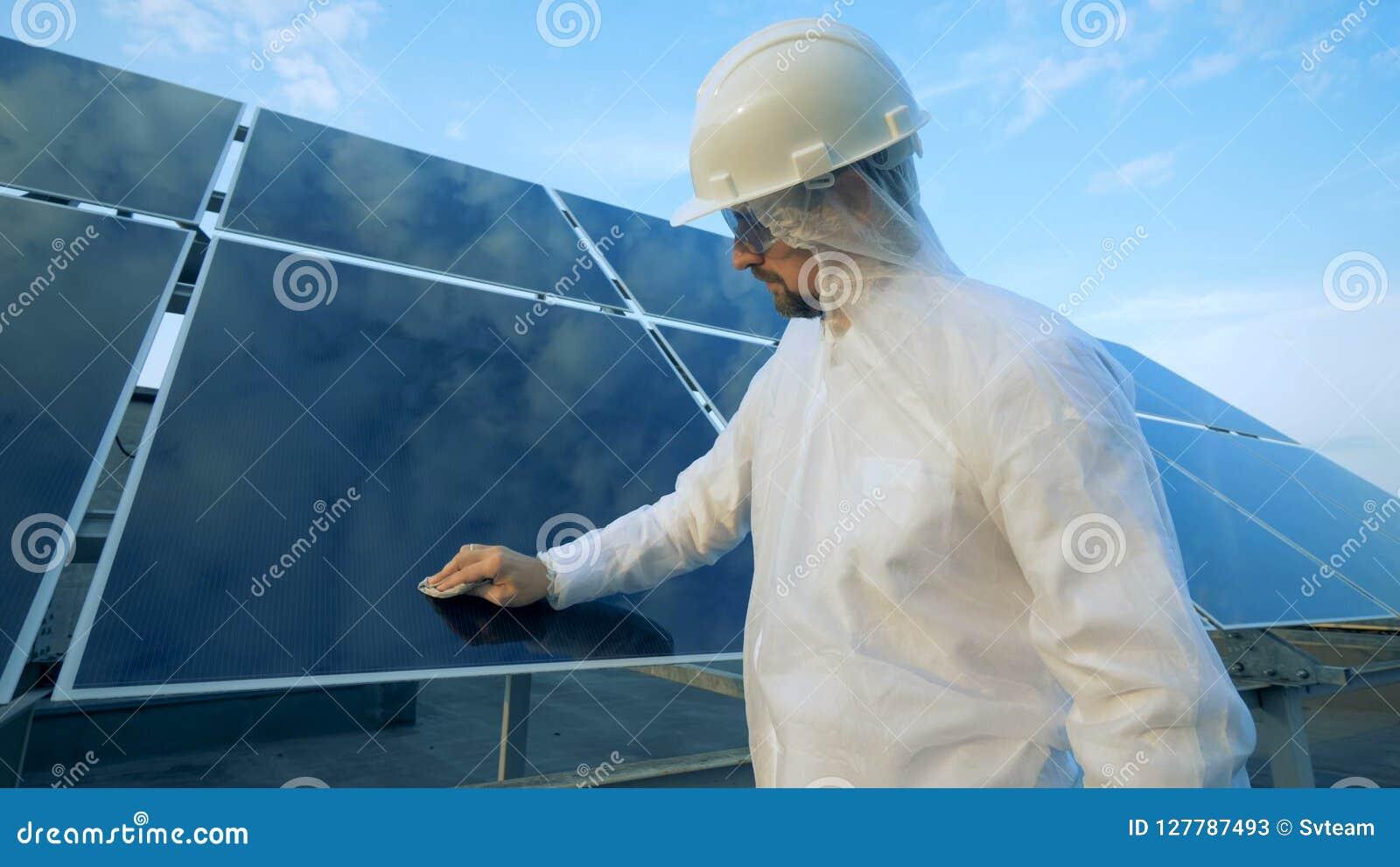 L ingegnere maschio pulisce il pannello solare