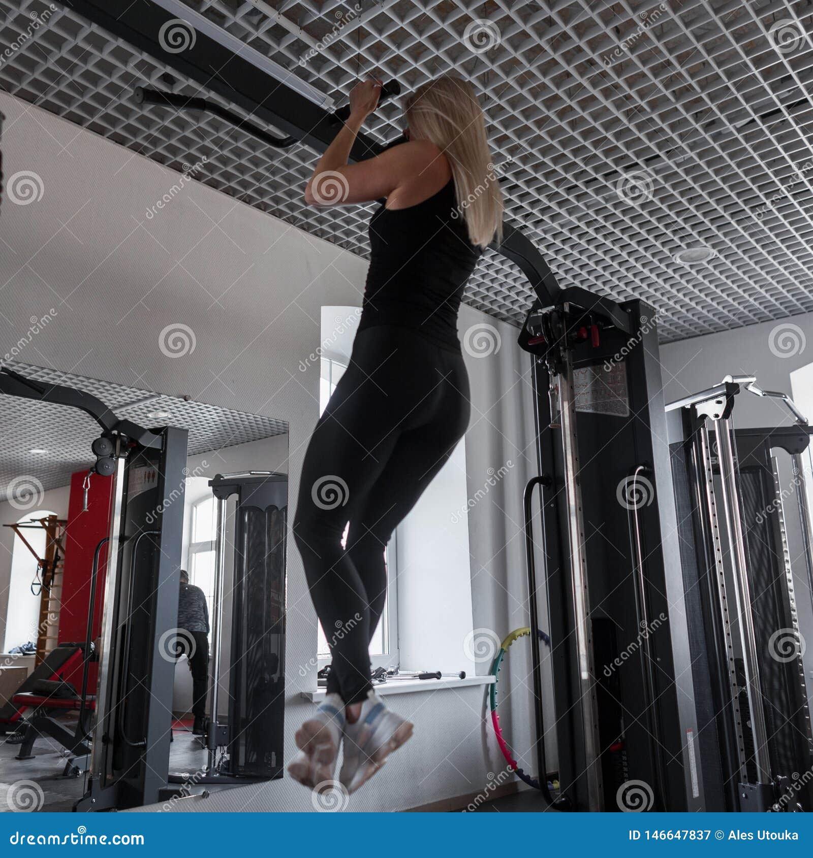L instructeur de jeune femme dans des vêtements noirs avec un beau corps tire vers le haut sur un simulateur en métal dans le gym