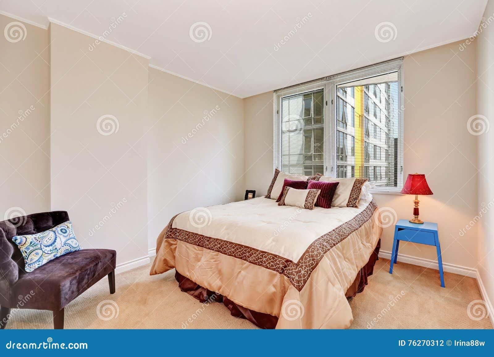 L intérieur beige simple de chambre à coucher avec des tons bruns et crémeux enfoncent