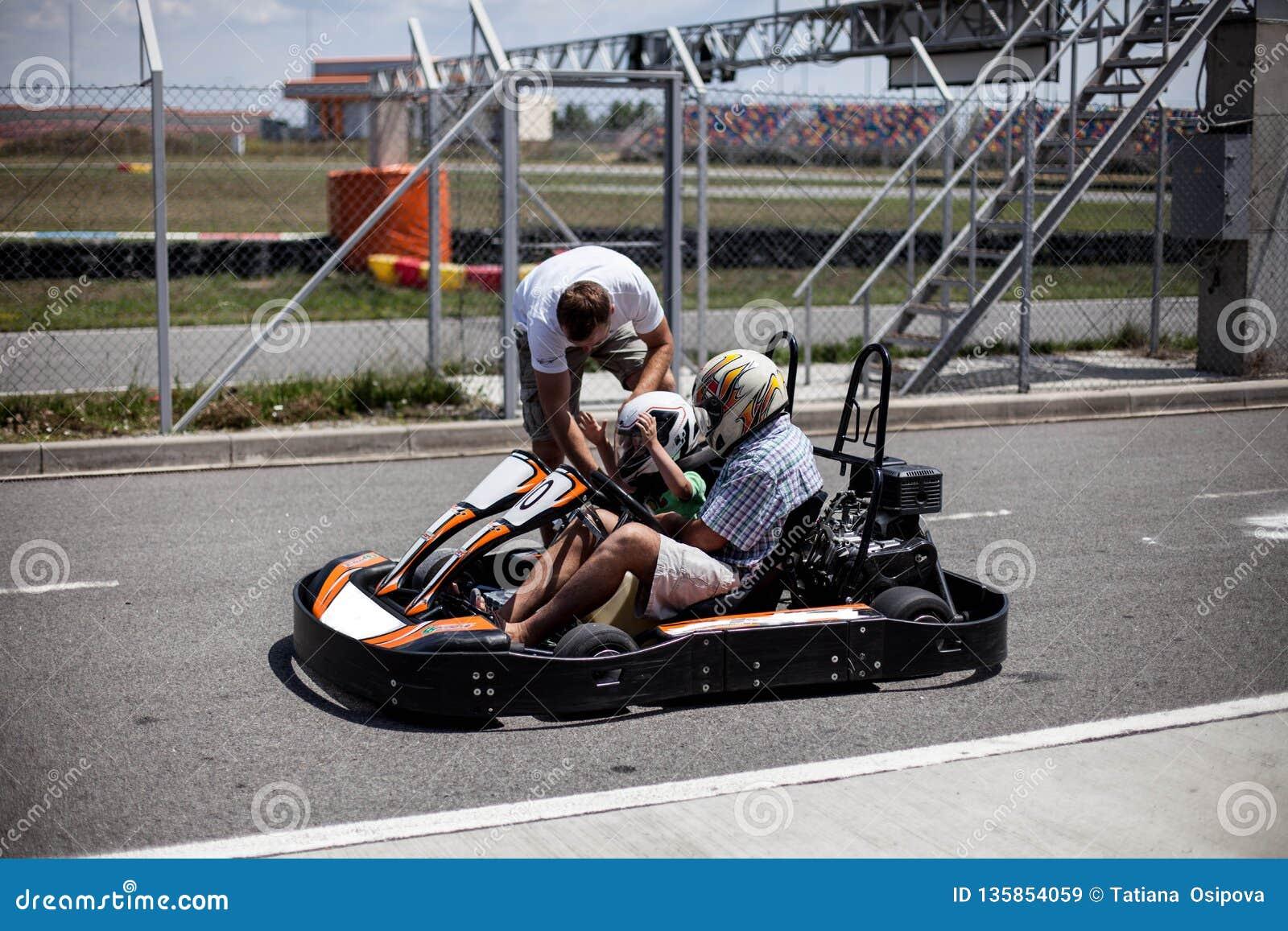 L istruttore della pista del kart aiuta il ragazzo a fissare il suo casco Accoppi karting Padre e figlio nella famiglia attiva di