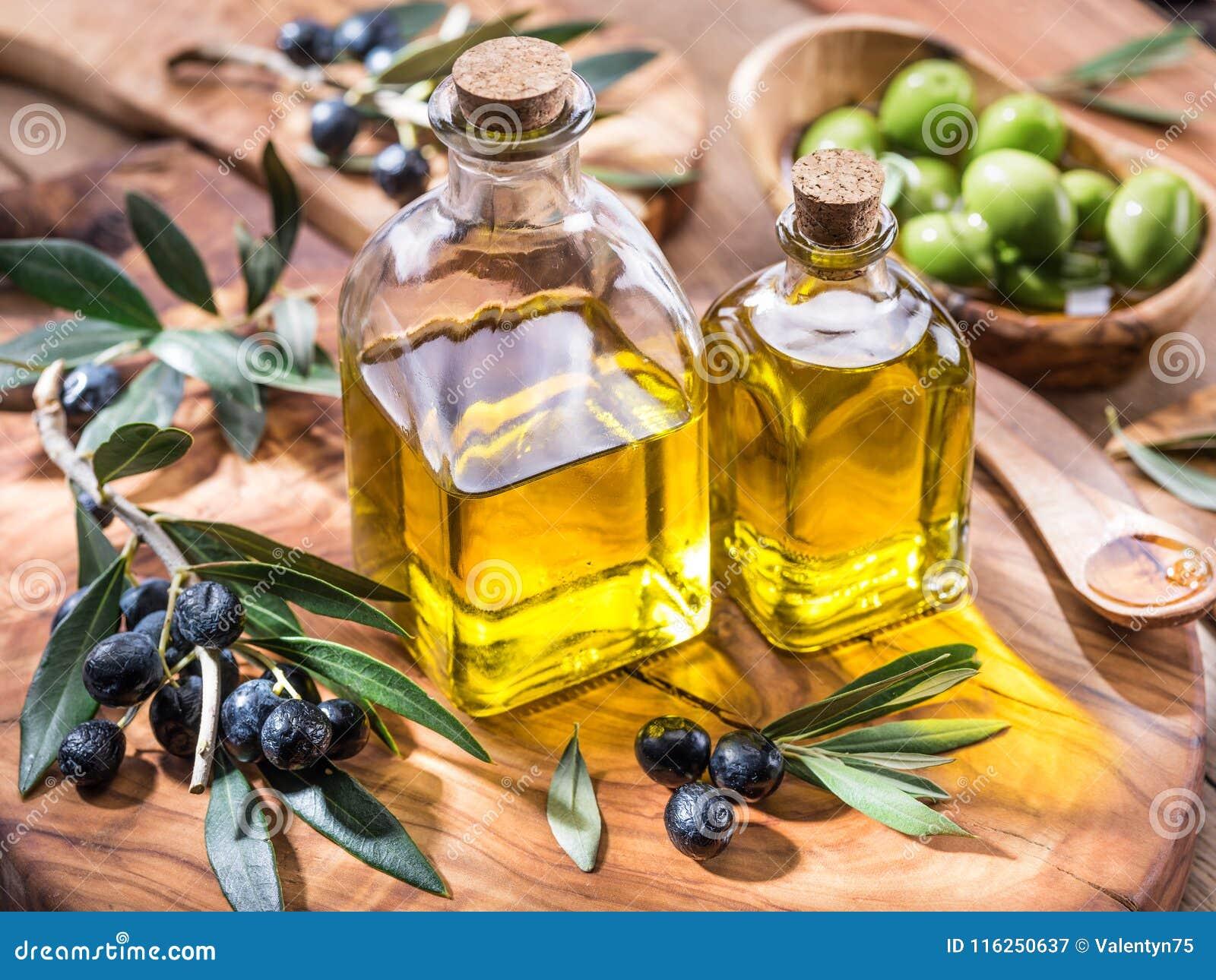 L olio d oliva e le bacche sono sul vassoio di legno verde oliva