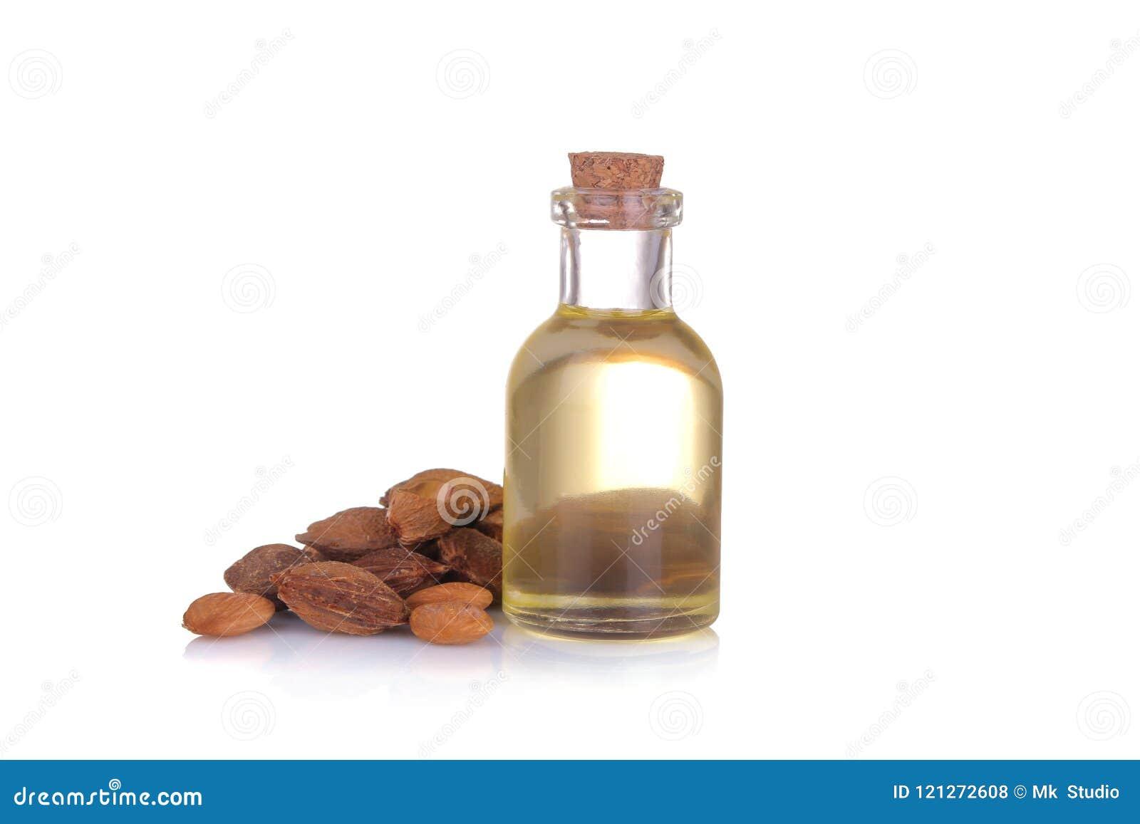 L olio di semi dell albicocca accanto alle ossa dell albicocca su un bianco ha isolato il fondo