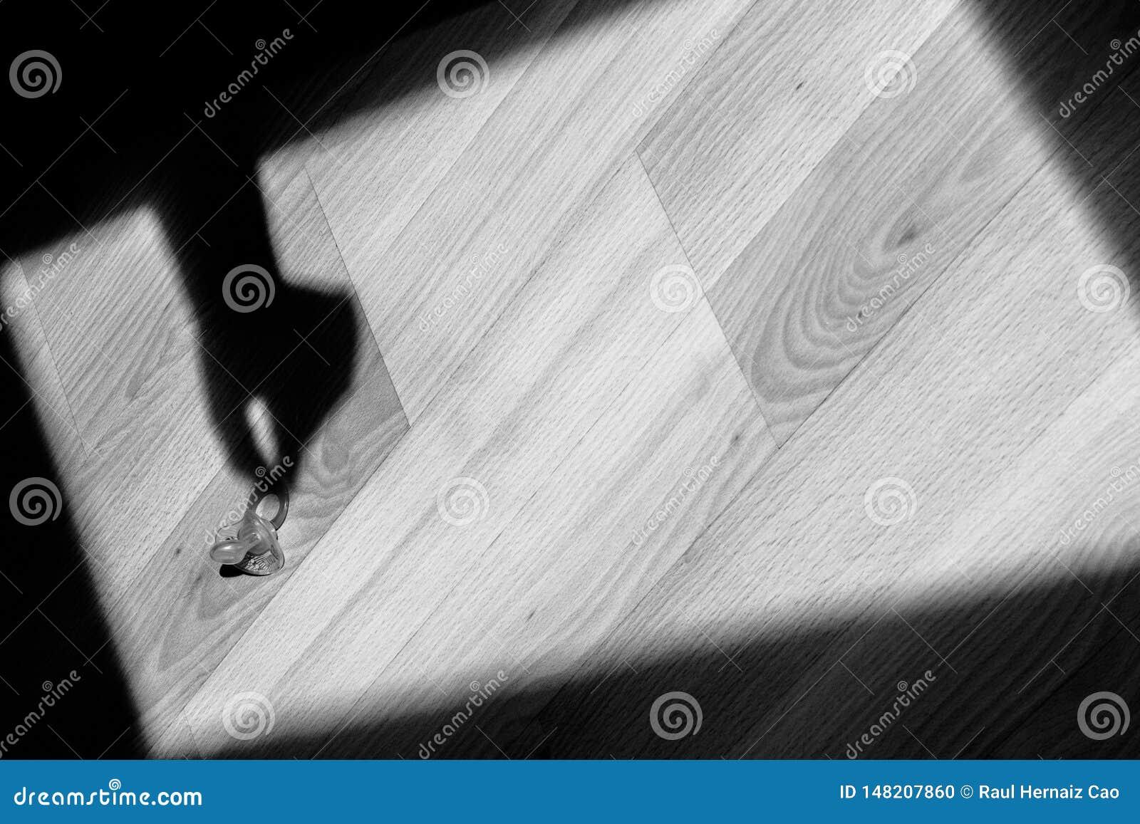 L ombre d une main prend une tétine du plancher Art abstrait, avec les symboles des enfants
