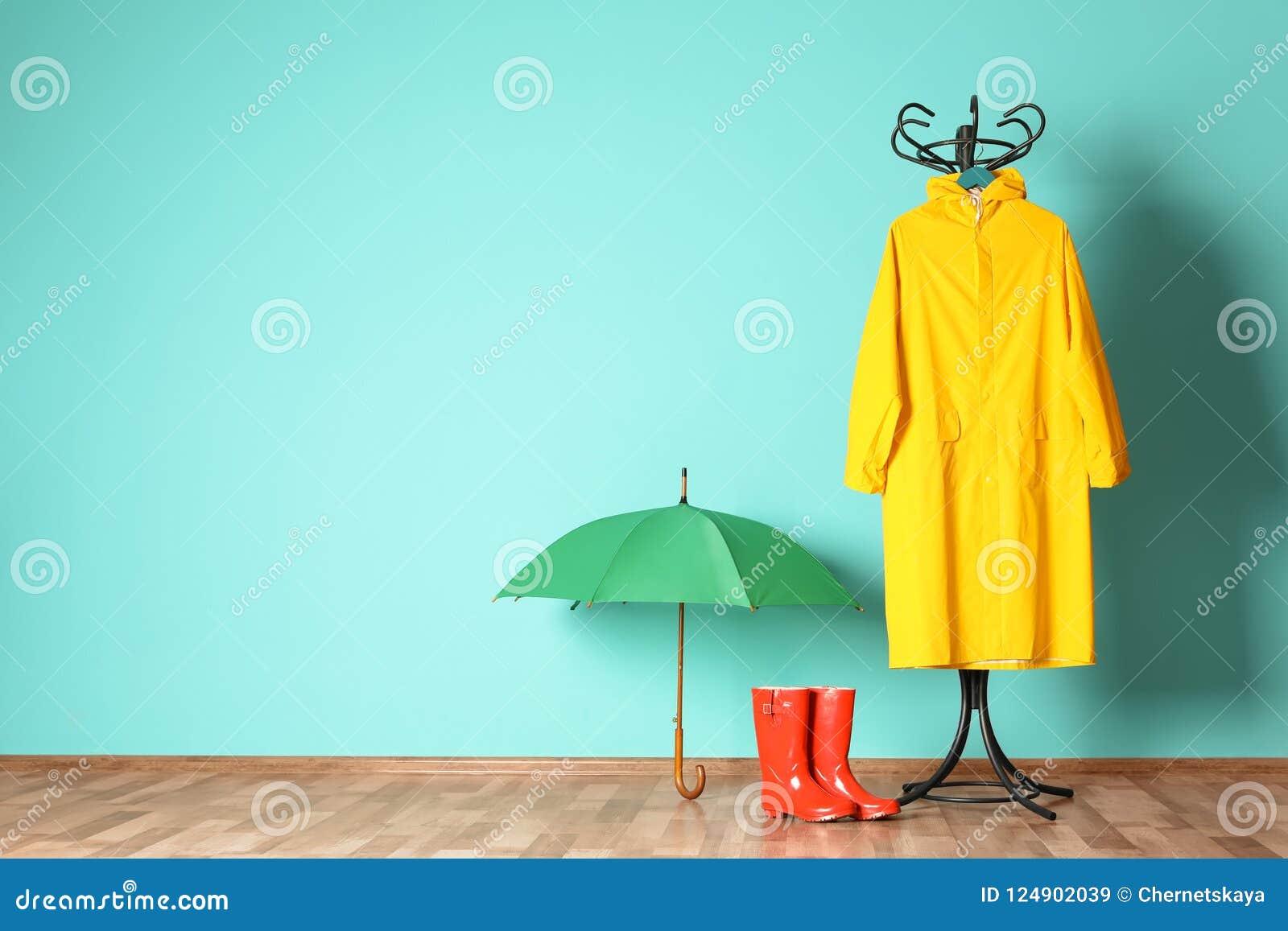 L ombrello, il cappotto di pioggia e gli stivali si avvicinano alla parete di colore