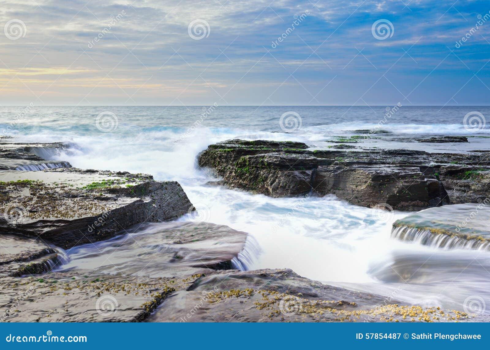 L onda circola sulle rocce stagionate e sui massi a Narrabeen del nord