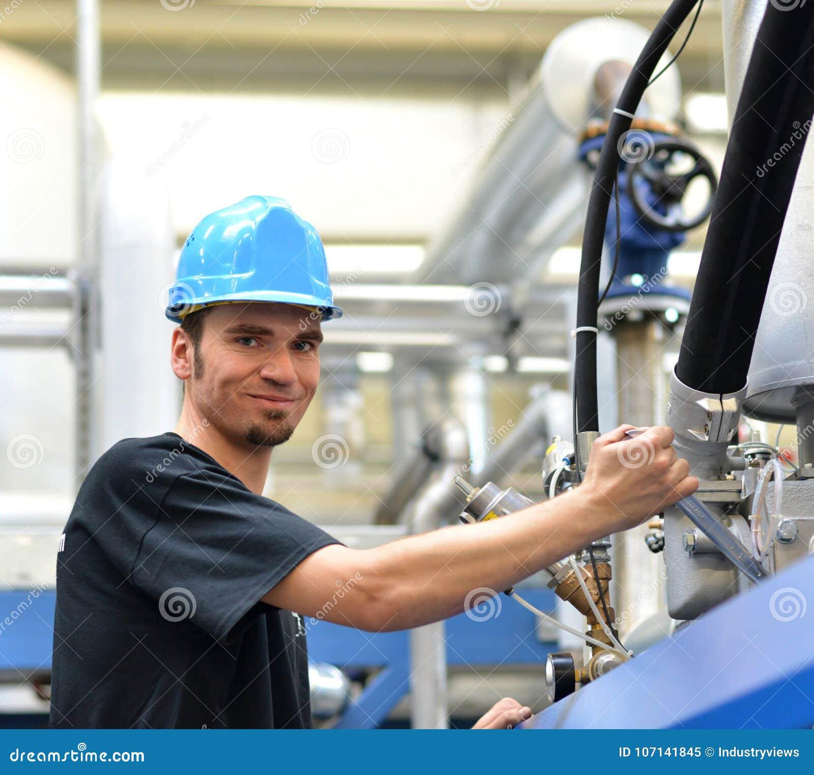 L operatore ripara una macchina in un impianto industriale con gli strumenti - p