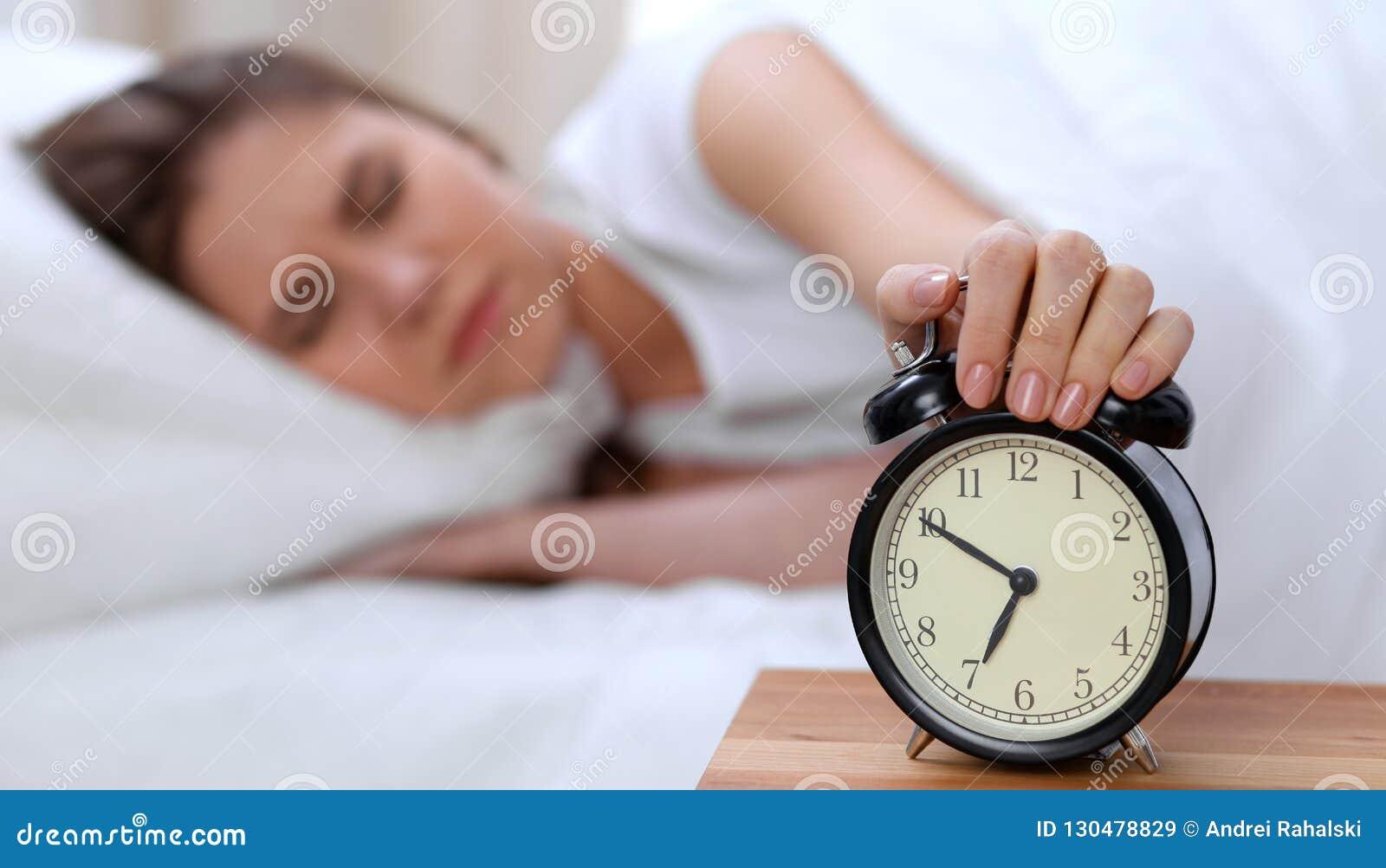 L opposé de réveil de la jeune femme somnolente étirant la main au disposé de sonnerie d alarme l arrêtent Réveillez-vous tôt, pa