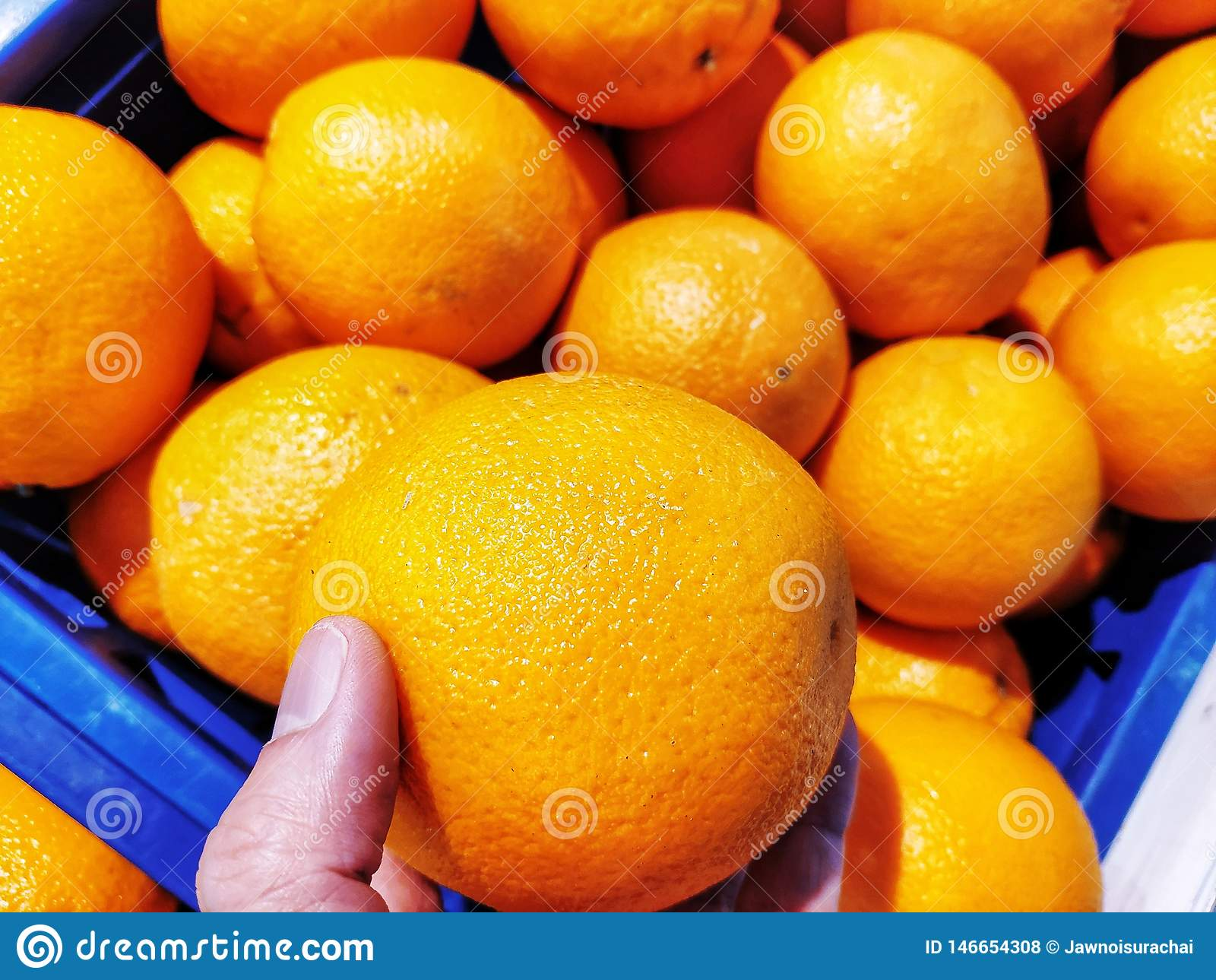 L orange est dans une main Beaucoup plus sont dans les coulisses dans un panier bleu