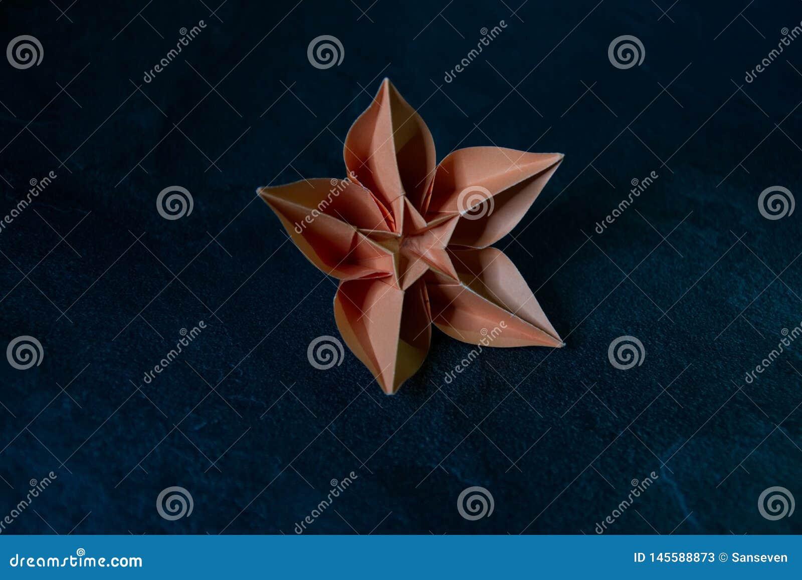 L origami fleurit la fleur - art de papier sur le fond texturisé
