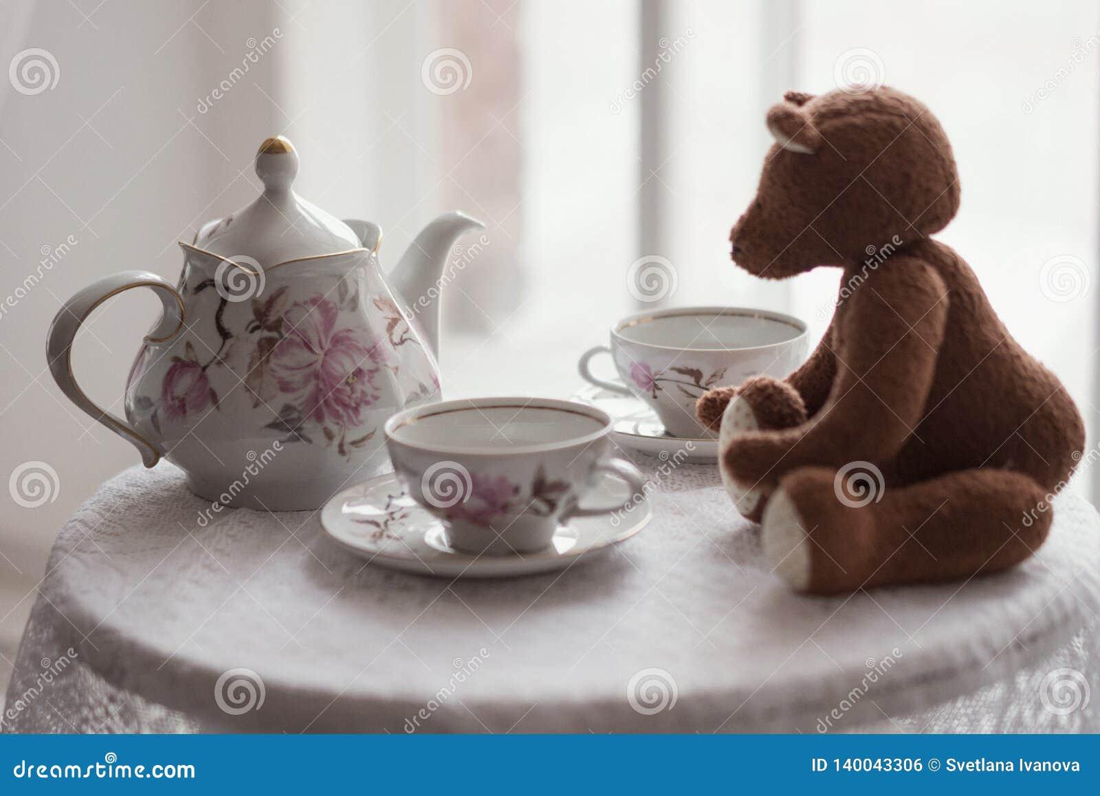 L orso del giocattolo di Brown si siede su una tavola con due tazze per tè e un bollitore