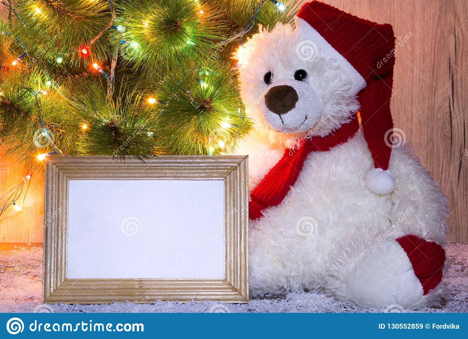 L orso di Natale, del nuovo anno che si siede sotto un albero di abete con i modelli di una struttura di legno per una foto o tes