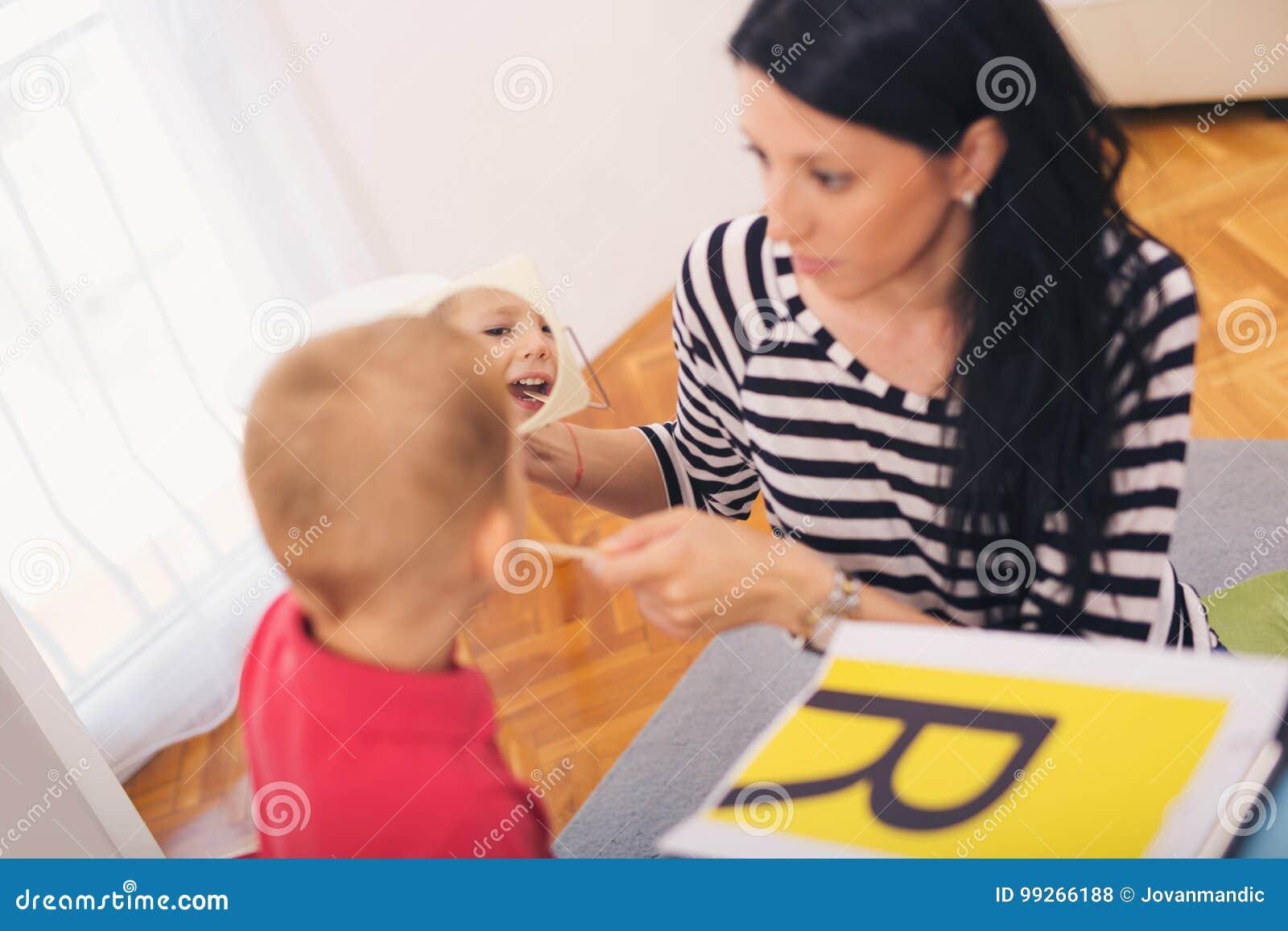 L orthophoniste enseigne les garçons à dire la lettre R