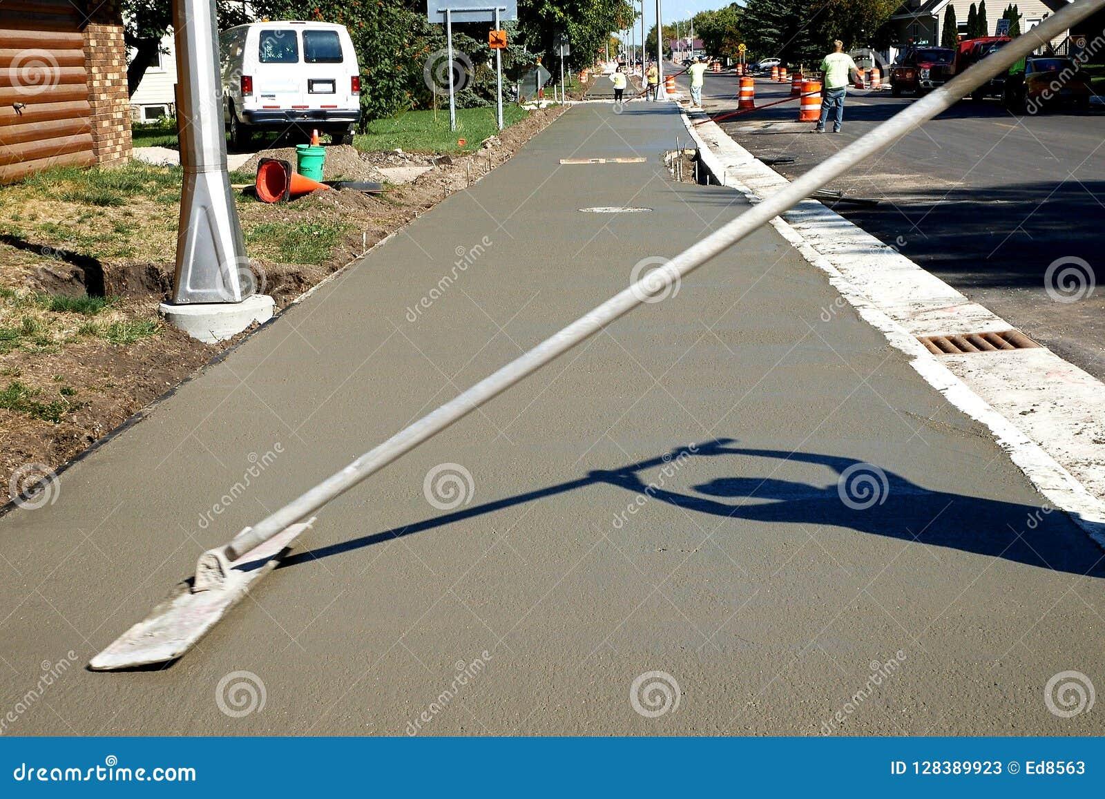 L ouvrier finit et lisse la surface en béton sur le nouveau trottoir