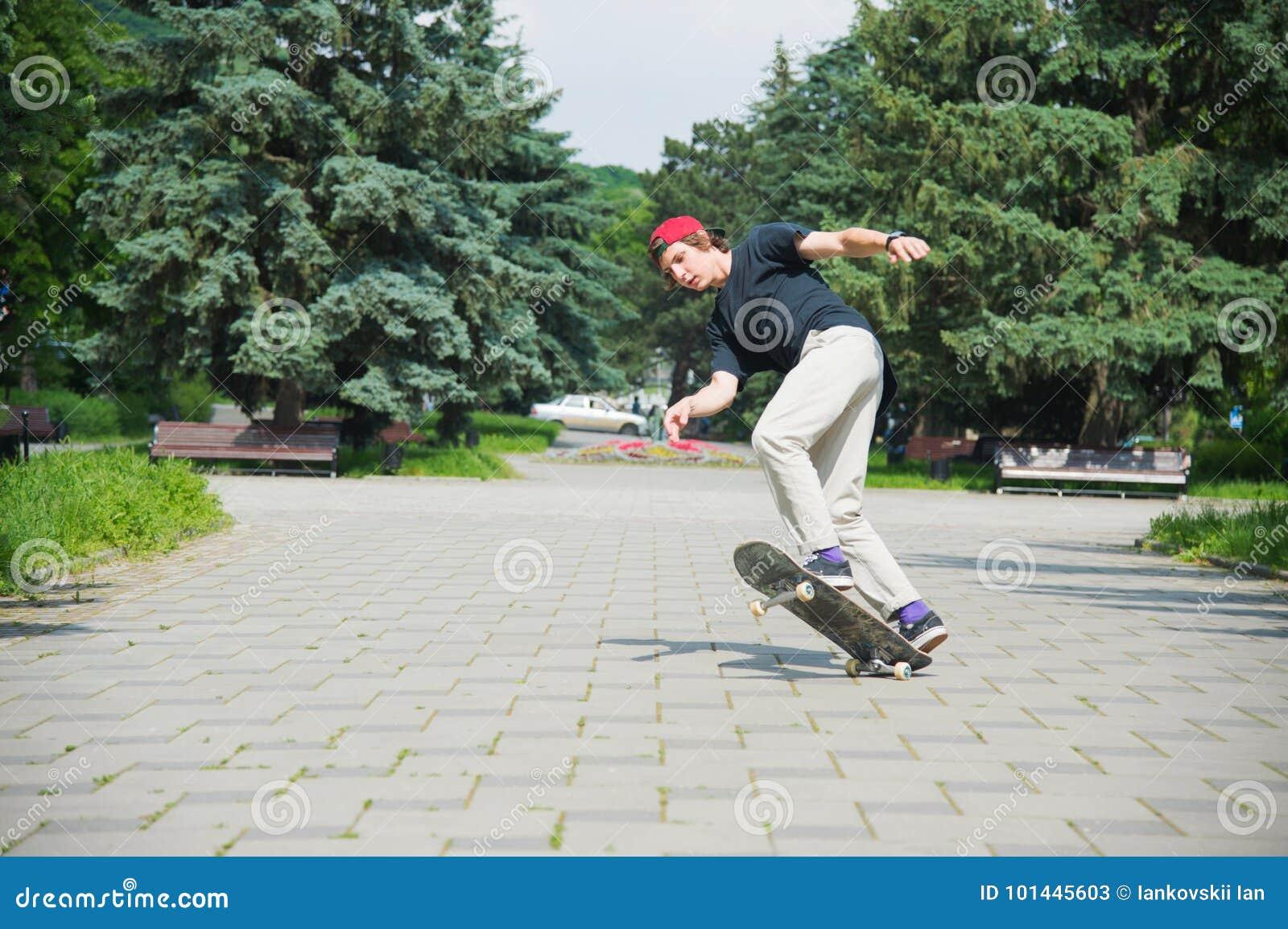 L pattinatore-adolescente dai capelli lunghi in una maglietta ed in un cappello della scarpa da tennis salta un vicolo contro un