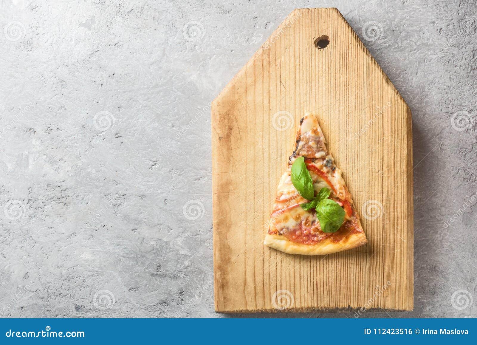 L un pezzo solo di pizza italiana con i pomodori si espande rapidamente bacon ed il formaggio ed il basilico va sul tagliere di l