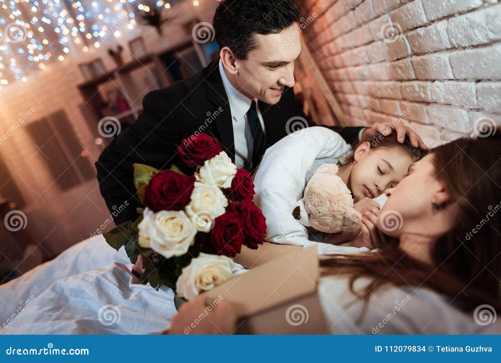 L uomo adulto con il mazzo delle rose è messo per inserire la piccola figlia per dormire Il bambino sta dormendo