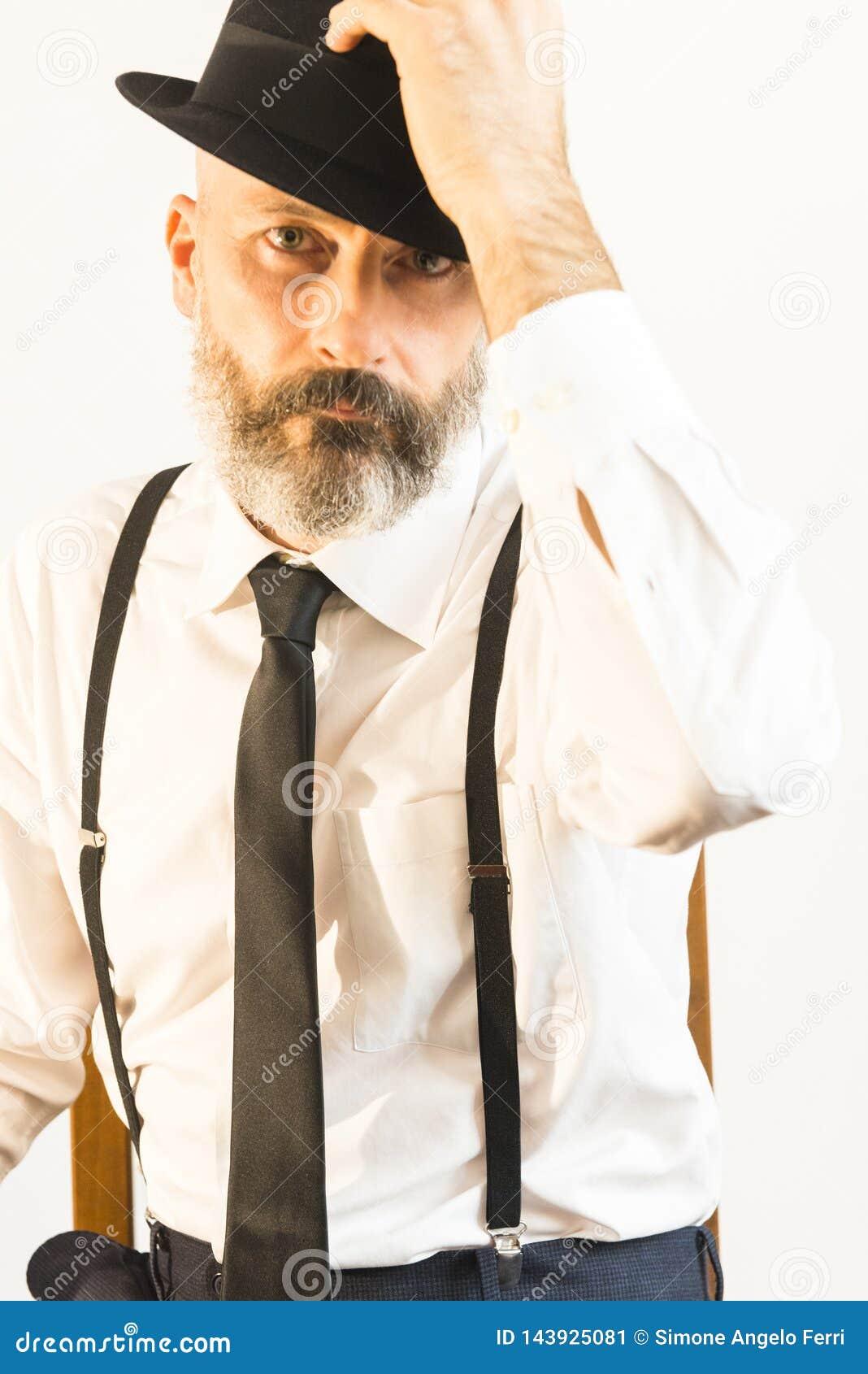 L uomo adulto prende il suo cappello con la mano sinistra