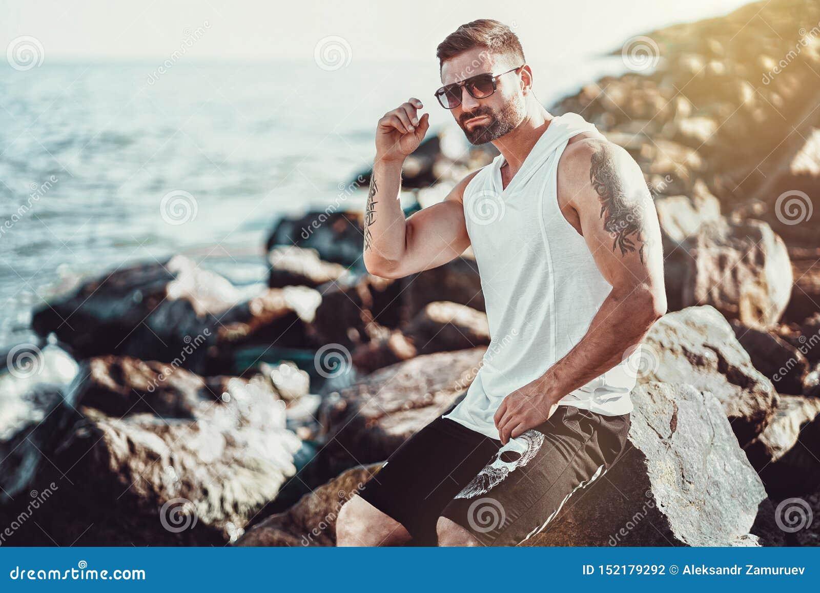 L uomo alla località di soggiorno in camicia bianca ed occhiali da sole che si siedono su una roccia sui precedenti del mare
