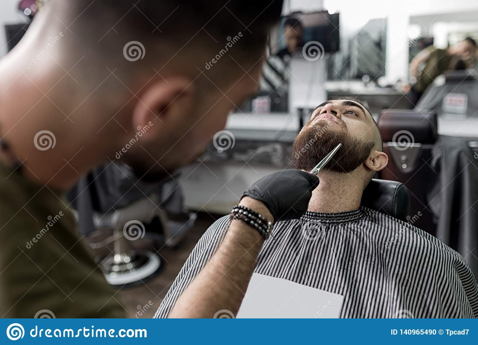 L uomo alla moda con una barba si siede ad un parrucchiere Il barbiere sistema la barba degli uomini con le forbici
