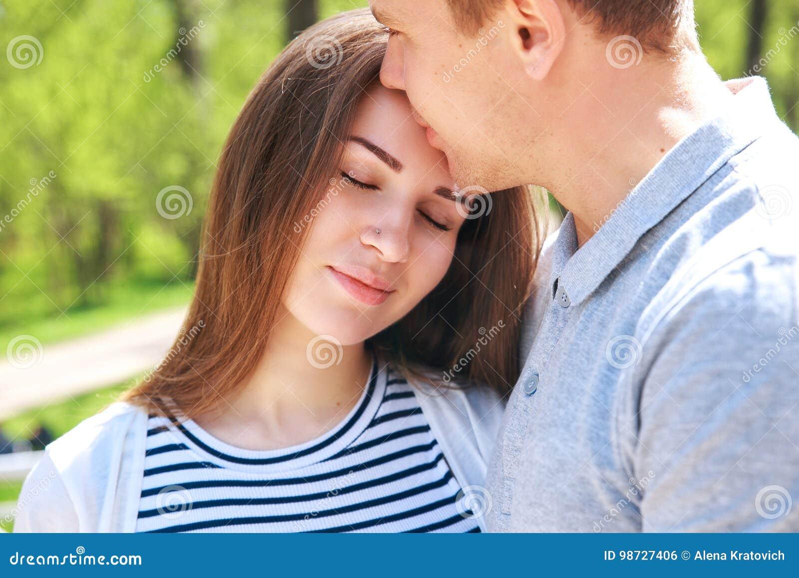 L uomo bello e la sua bella moglie incinta sono abbraccianti e sorridenti mentre stanno nel parco