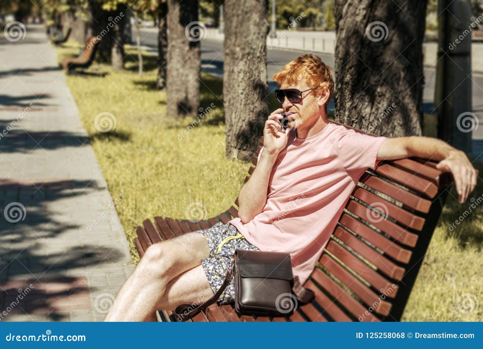 L uomo che parla dal telefono sul banco nel parco