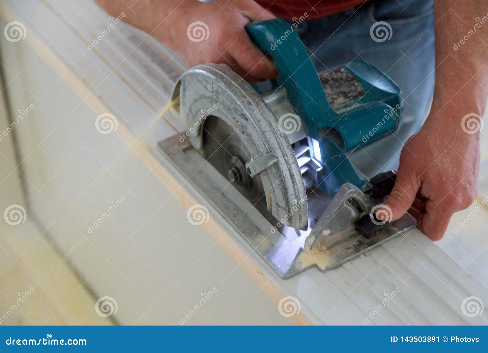 L uomo che usando una circolare ha visto per il taglio del rinnovamento domestico del legno del costruzione della porta e, strume