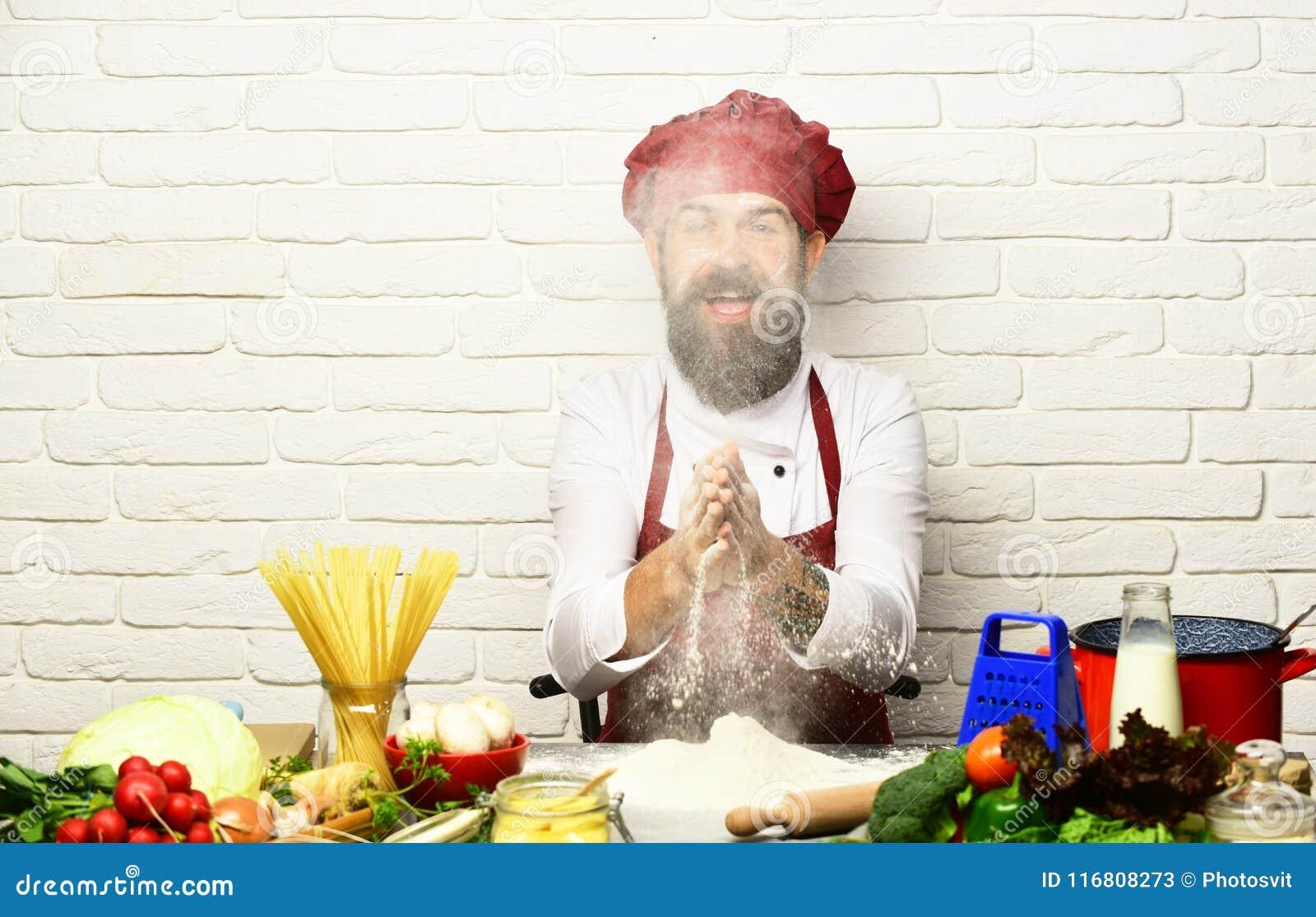 L uomo con la barba gioca con farina sul fondo bianco del mattone