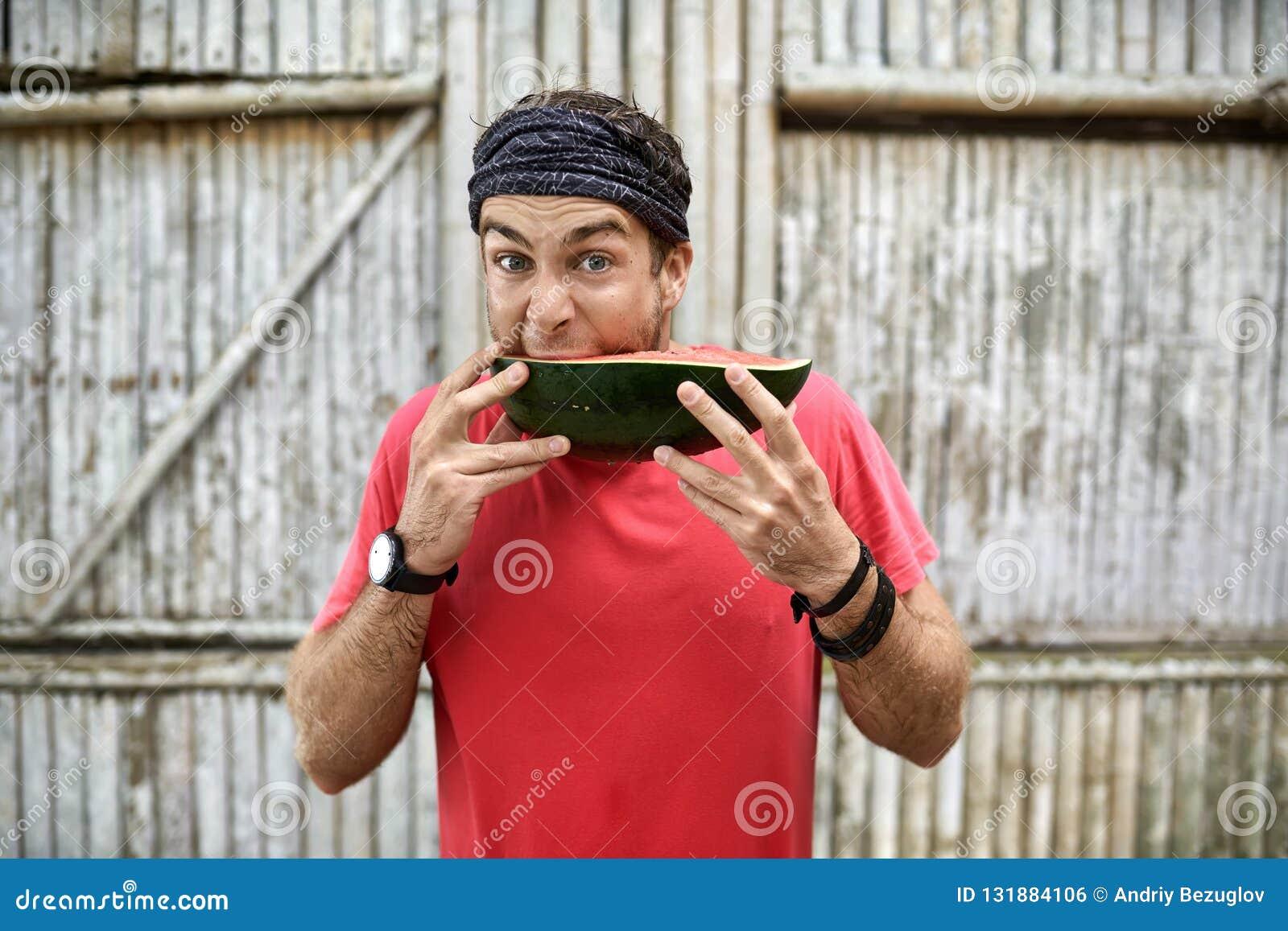 L uomo con stoppia con espressione facciale divertente sta mangiando l anguria