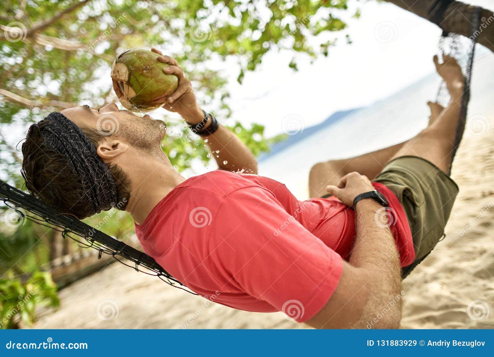 L uomo con stoppia sta bevendo dalla noce di cocco sull amaca sulla spiaggia di sabbia