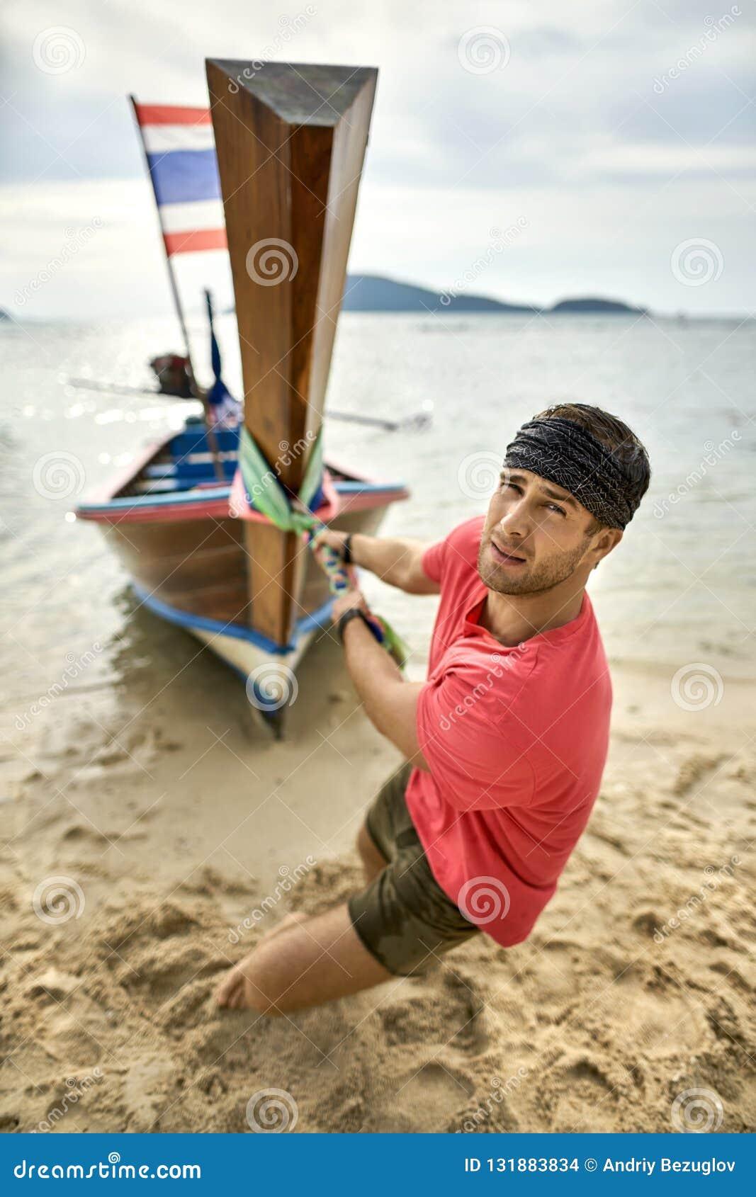 L uomo con stoppia sta tirando la barca di legno dalla corda sulla spiaggia di sabbia