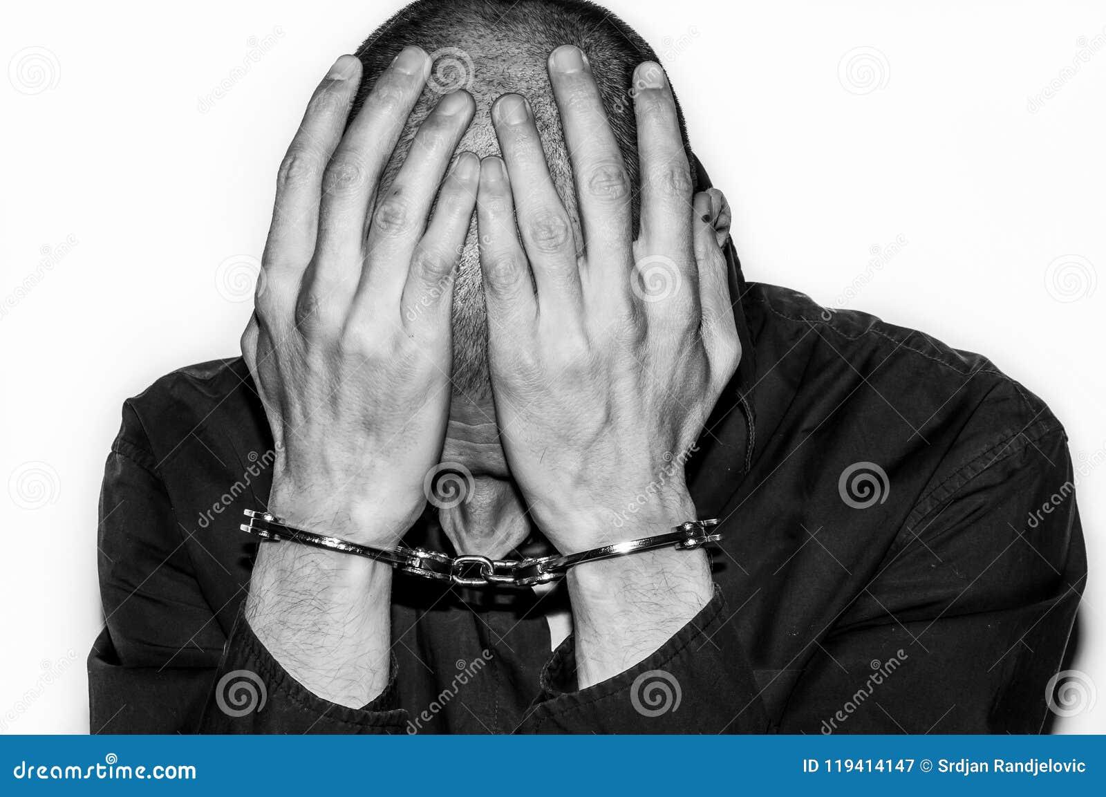 L uomo criminale arrestato e ammanettato con le manette sulle sue mani riguarda la sua testa e si rammarica di nel commissariato
