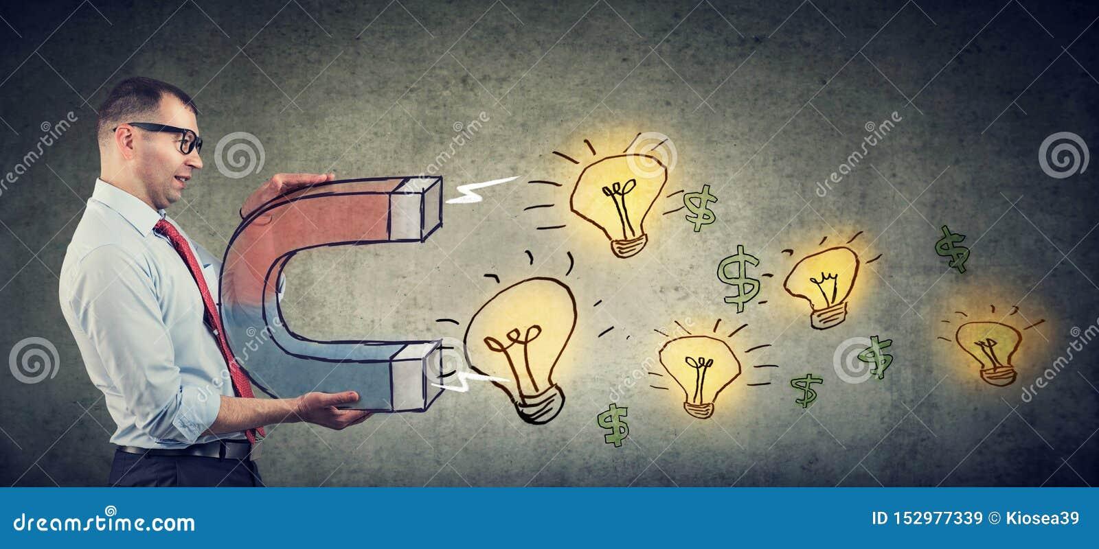L uomo d affari attira le lampadine di idee luminose con un grande magnete