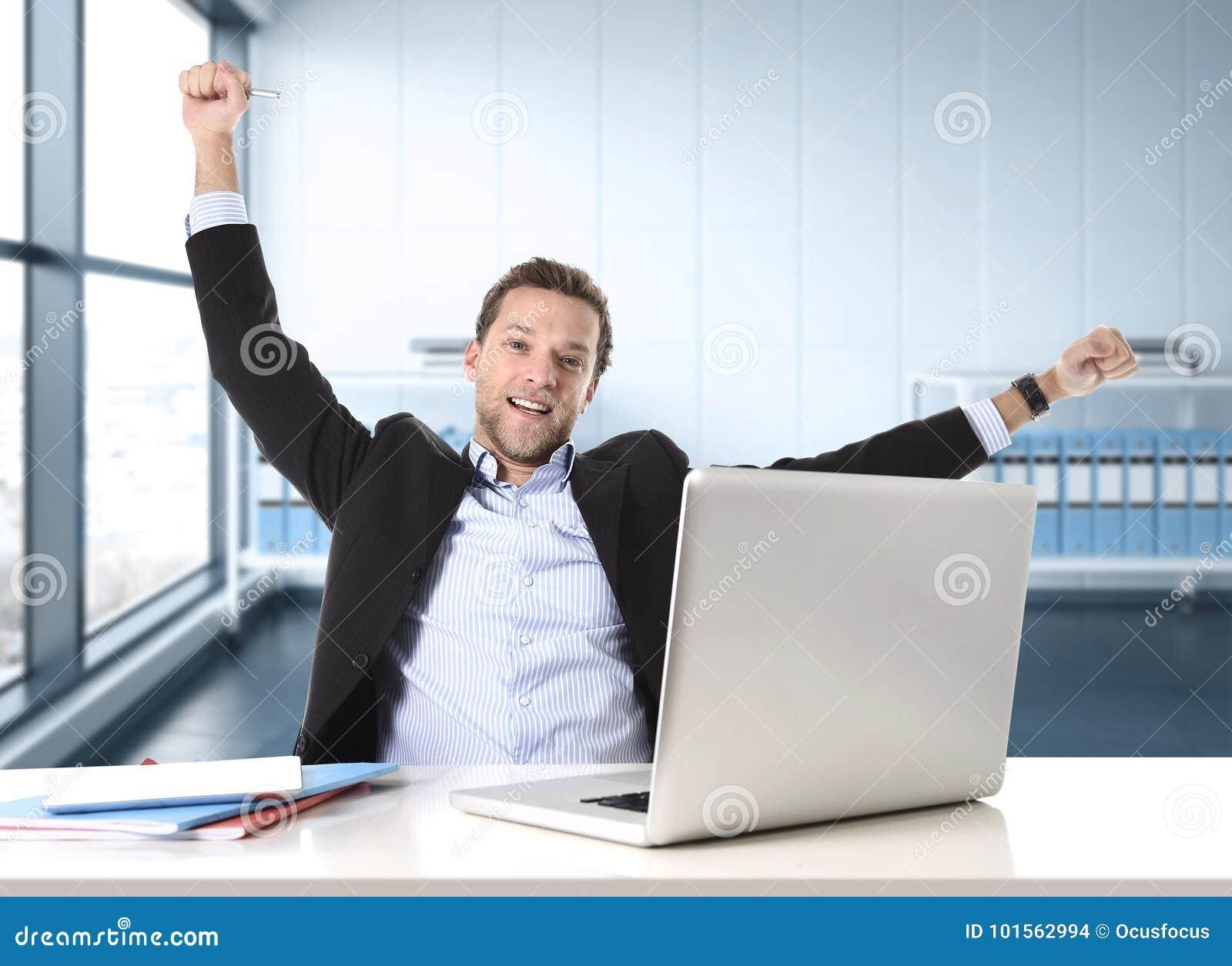 L uomo d affari attraente felice ed intenso sul lavoro d ufficio che si siede allo scrittorio del computer ha soddisfatto la cele