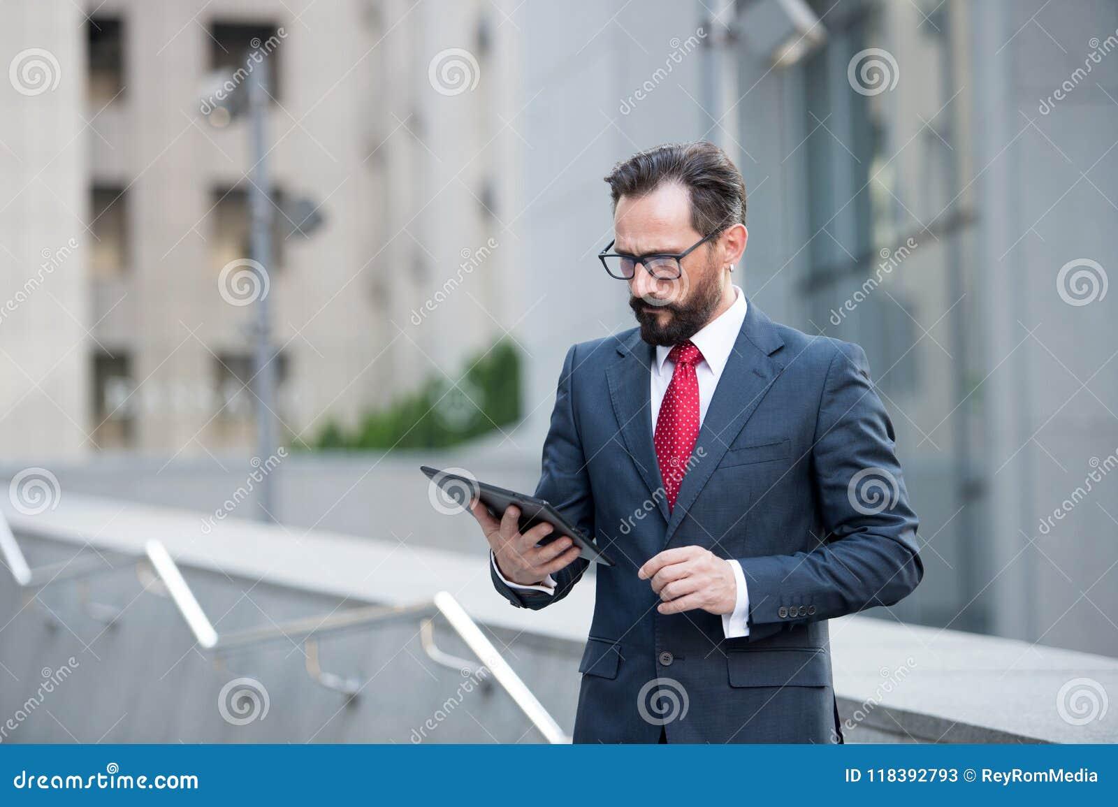 L uomo d affari attraente in vestito ed il legame rosso controllano o leggono l edificio per uffici all aperto della compressa di