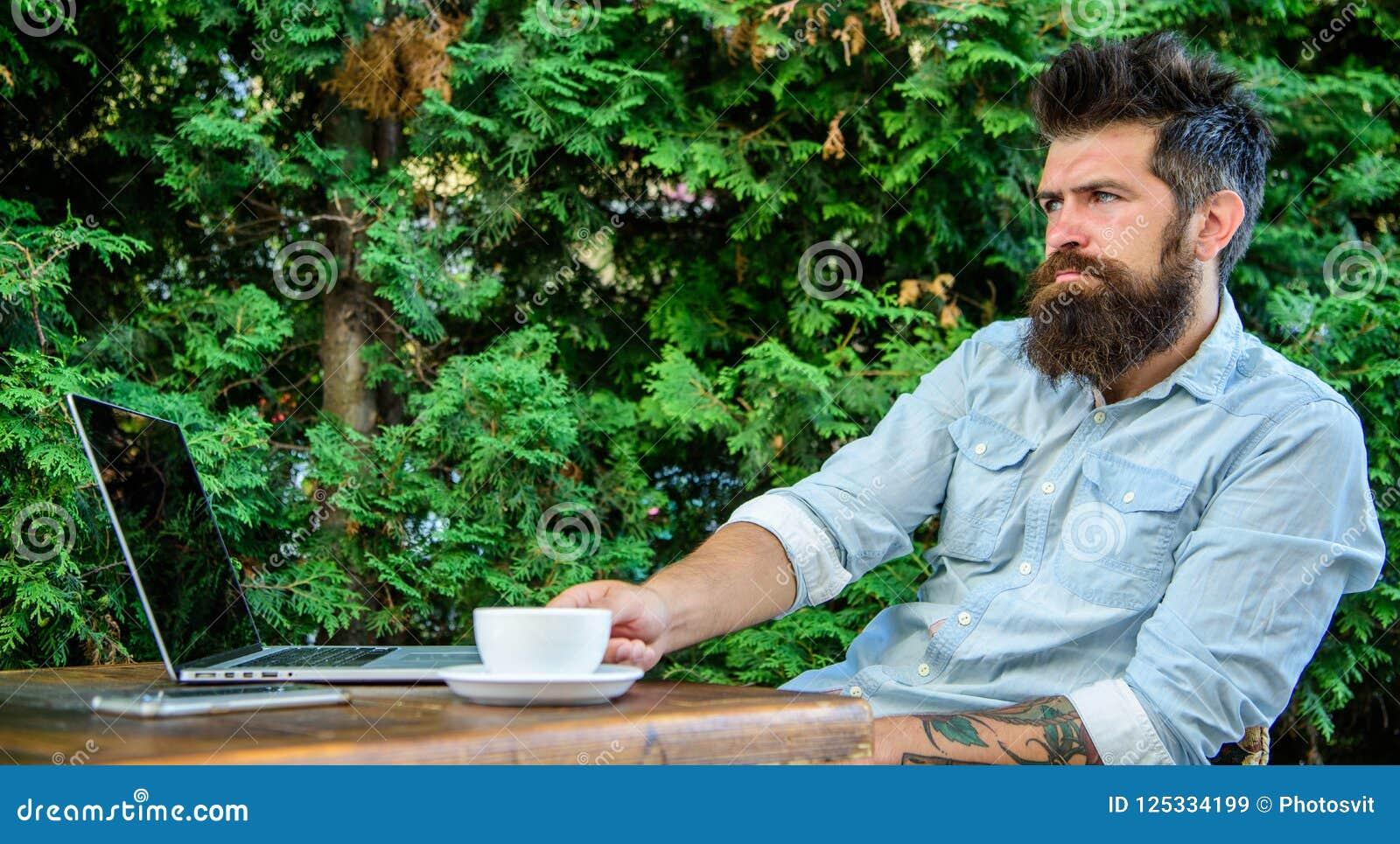 L uomo d affari barbuto dell uomo si siede il terrazzo con il computer portatile e la tazza di caffè Freelance il beneficio Crei