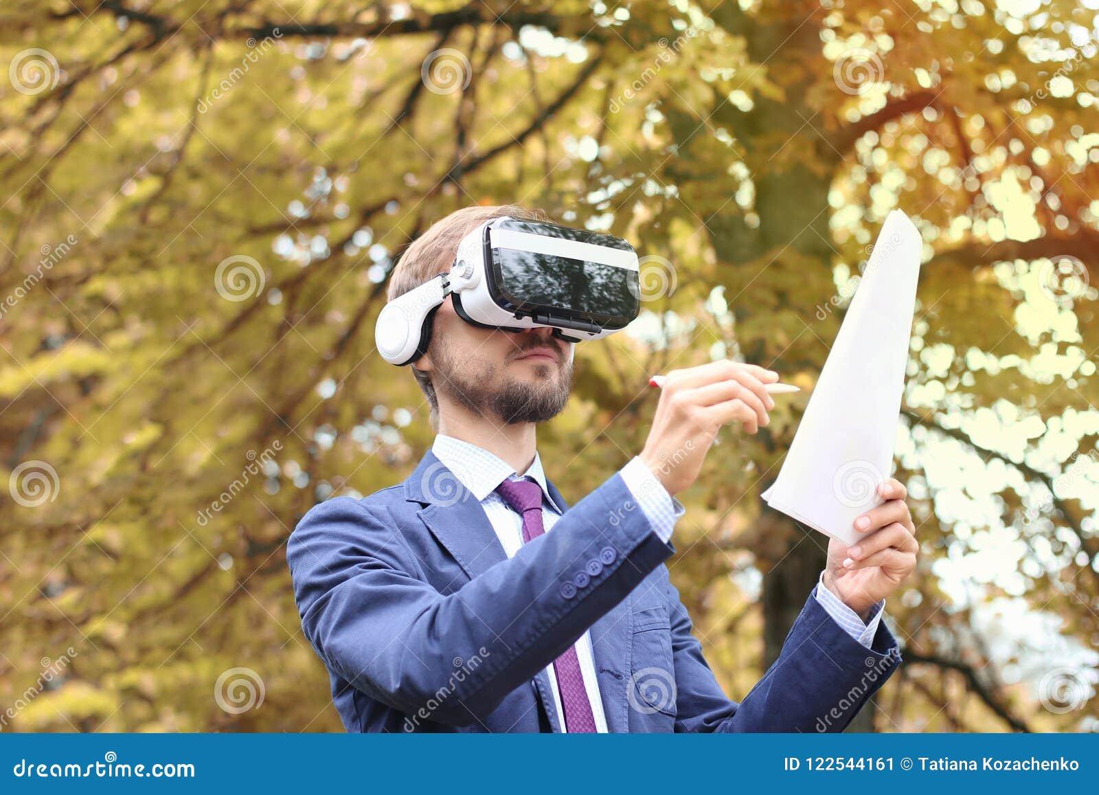 L uomo d affari barbuto felice con i vetri di realtà virtuale firma i documenti nel parco di autunno Firma elettronica, tecnologi