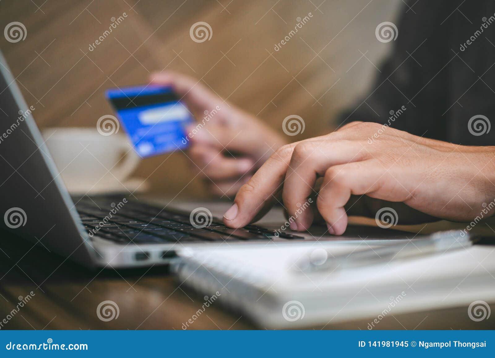 L uomo d affari che tiene la carta di credito e che scrive sul computer portatile per acquisto ed il pagamento online fa un acqui