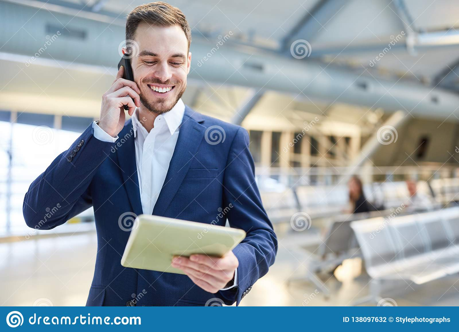 L uomo d affari con il PC ed il telefono cellulare della compressa è soddisfatto