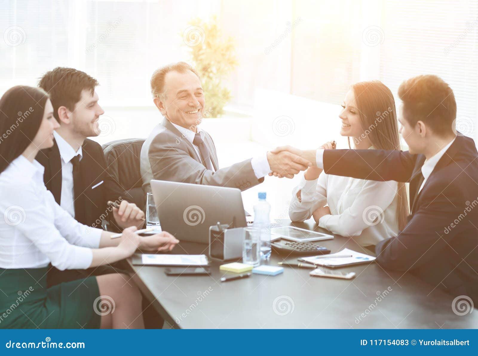 L uomo d affari e l investitore stringono le mani al tavolo delle trattative