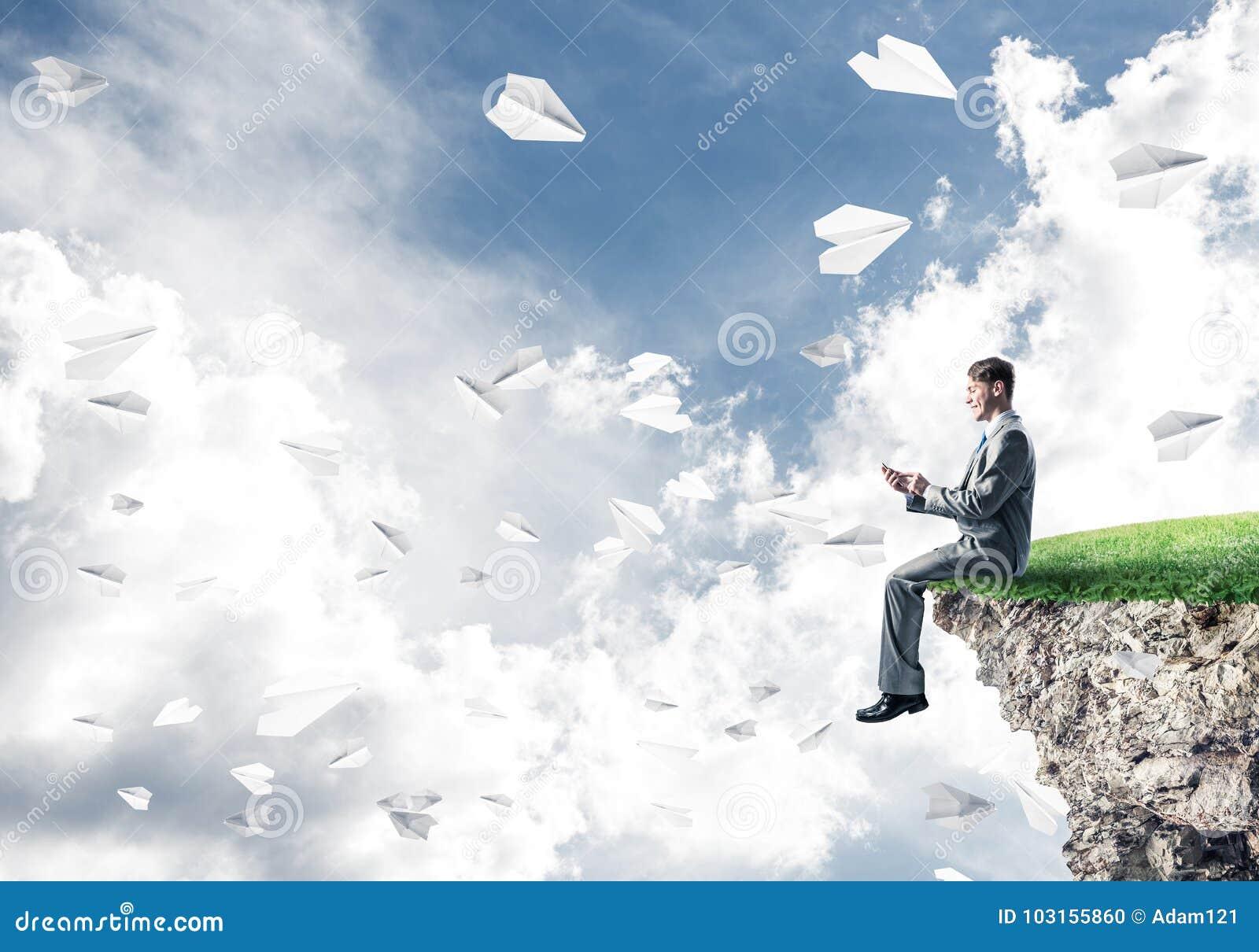 L uomo d affari elegante sul bordo della roccia che fa le chiamate e la carta spiana la f