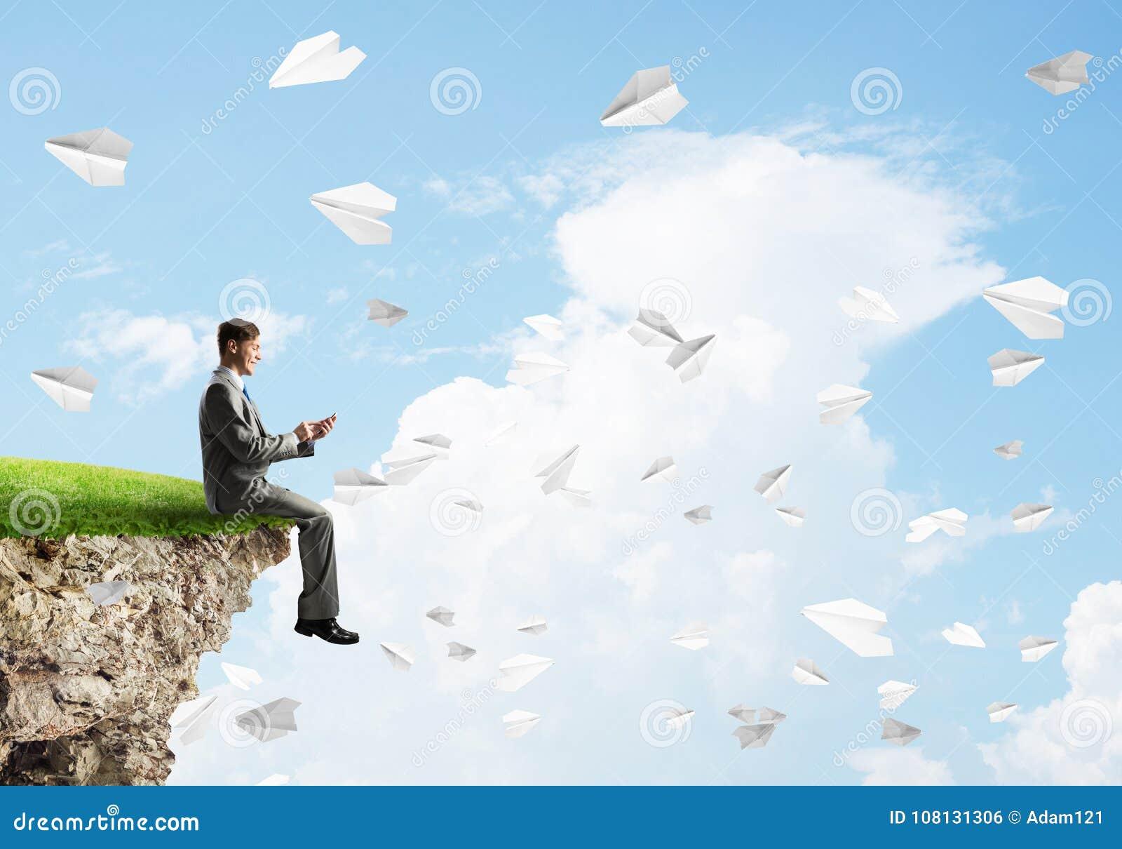 L uomo d affari elegante sul bordo della roccia che fa le chiamate e la carta spiana il volo intorno