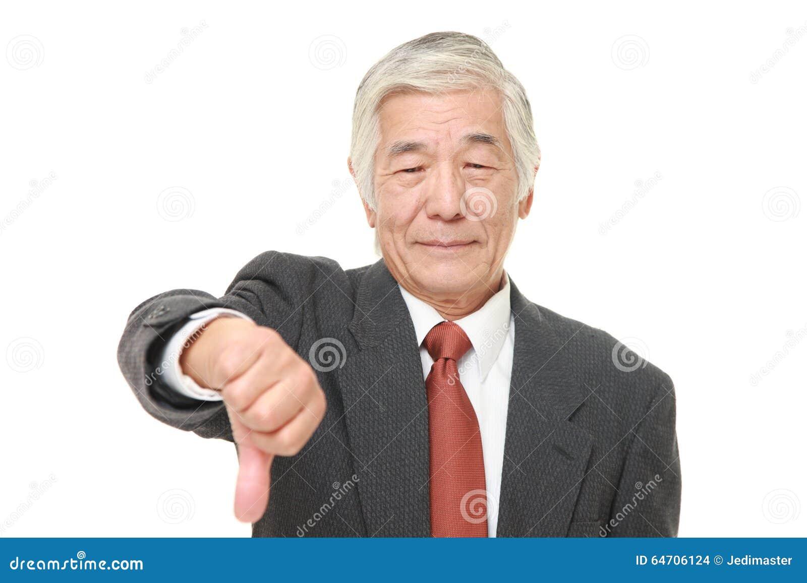 L uomo d affari giapponese senior con i pollici giù gesture