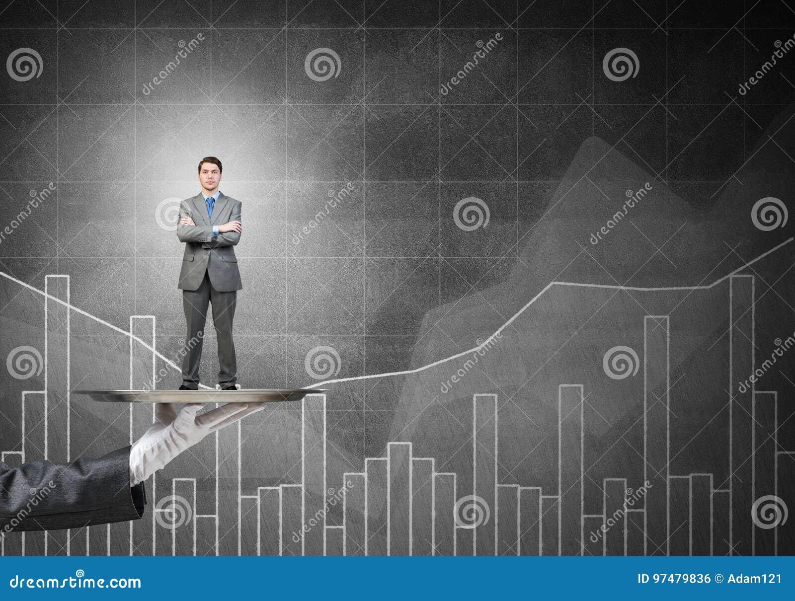 L uomo d affari sicuro ha presentato sul vassoio del metallo contro i grafici e diagrams il fondo