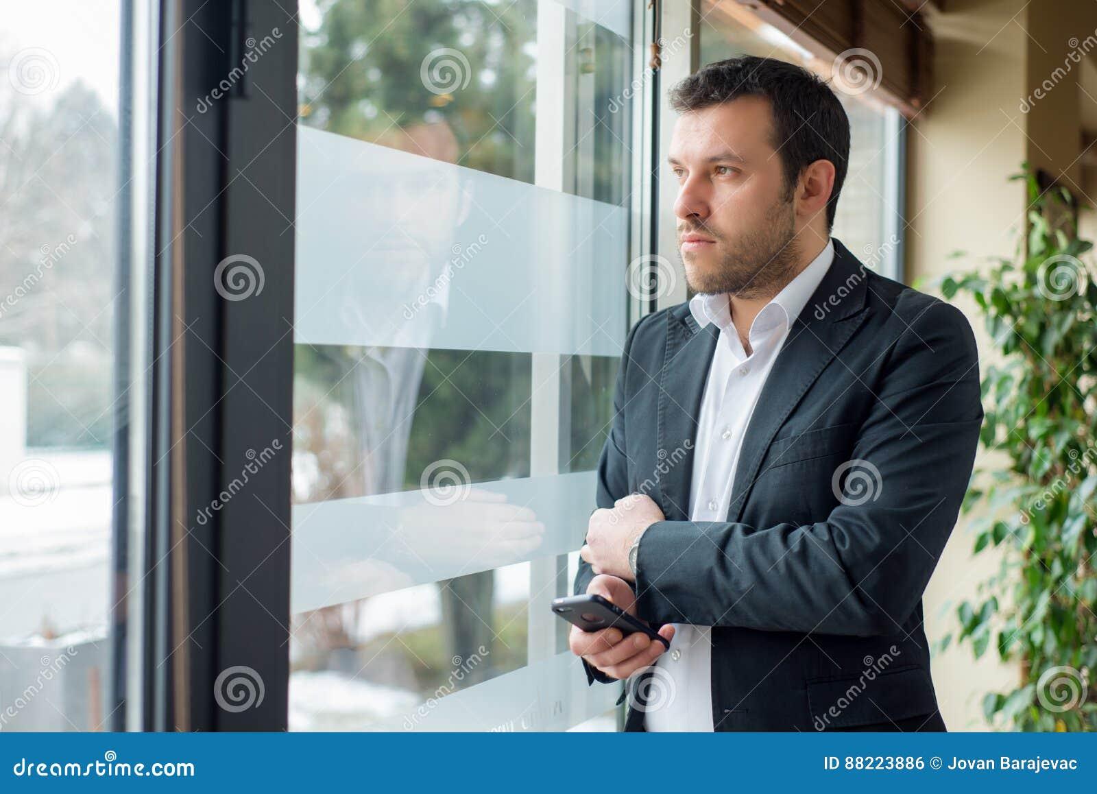 L uomo d affari sta guardando la depressione la finestra
