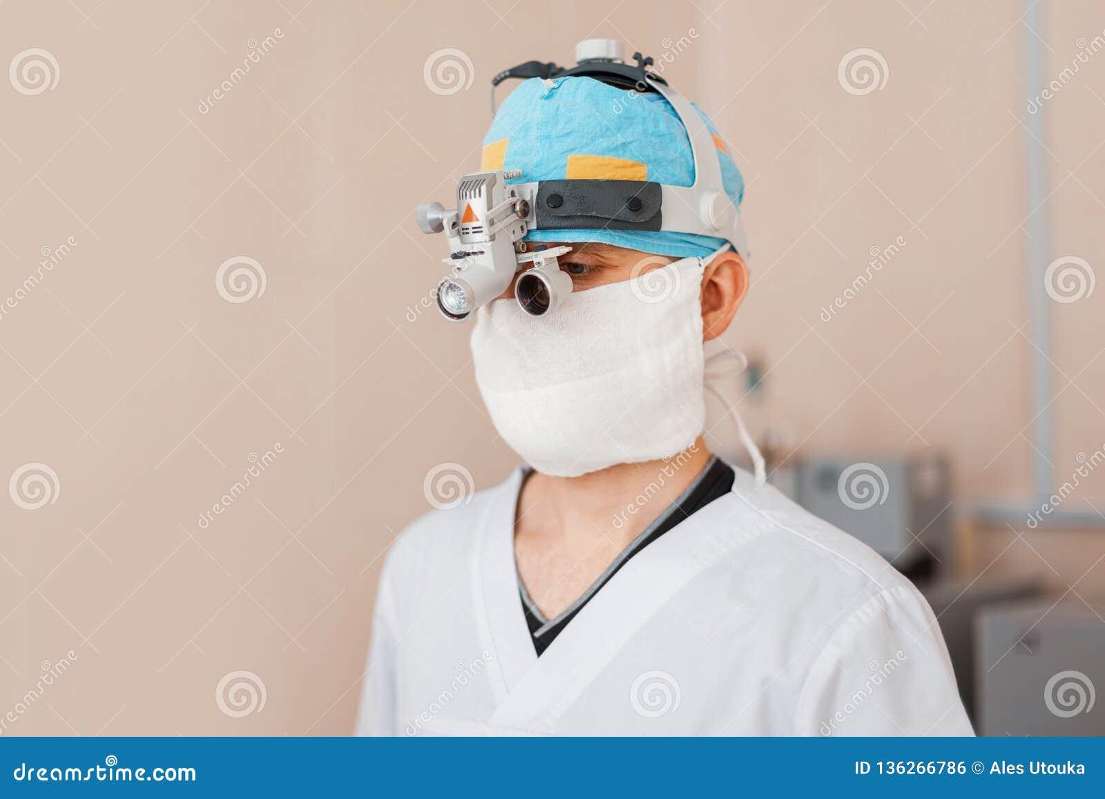 L uomo del chirurgo in una maschera in vestiti medici speciali che indossano i vetri con lenti di ingrandimento d ingrandimento b